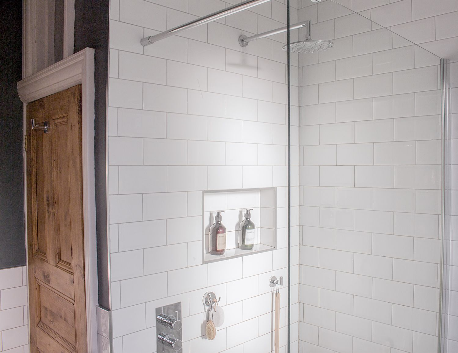 A photo of the new open shower area with one panel screen and a niche for toiletries.