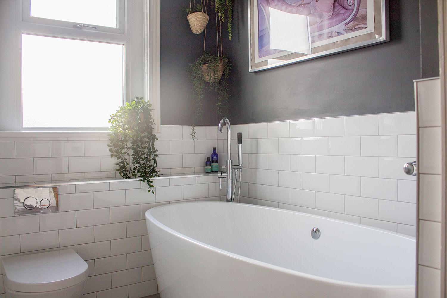 A photo of the bathroom showing the bath, window with new blind, dark walls and metro tiles with hanging planters.