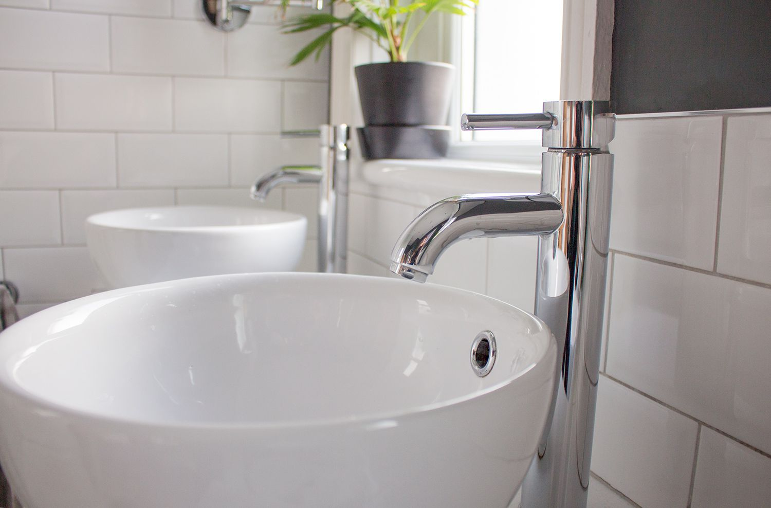 A close up of the two sinks with their tall chrome taps next to them.