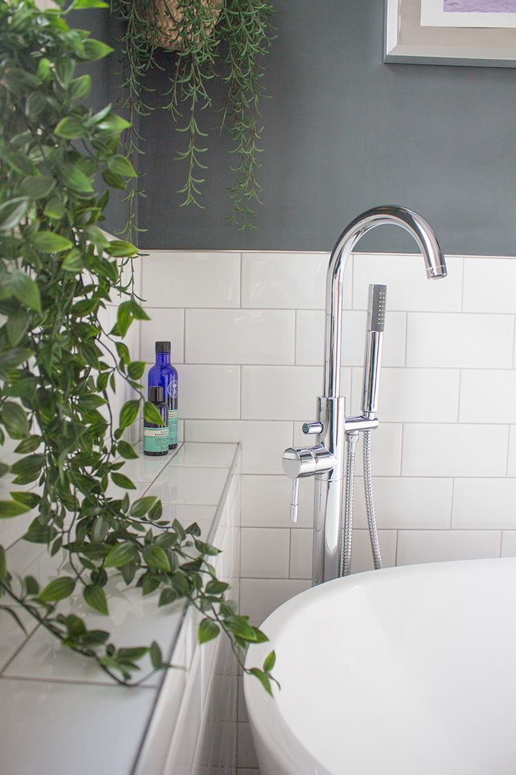 A close up of the standpipe bath tap and shower head, seen through the plant hanging over the window sill.