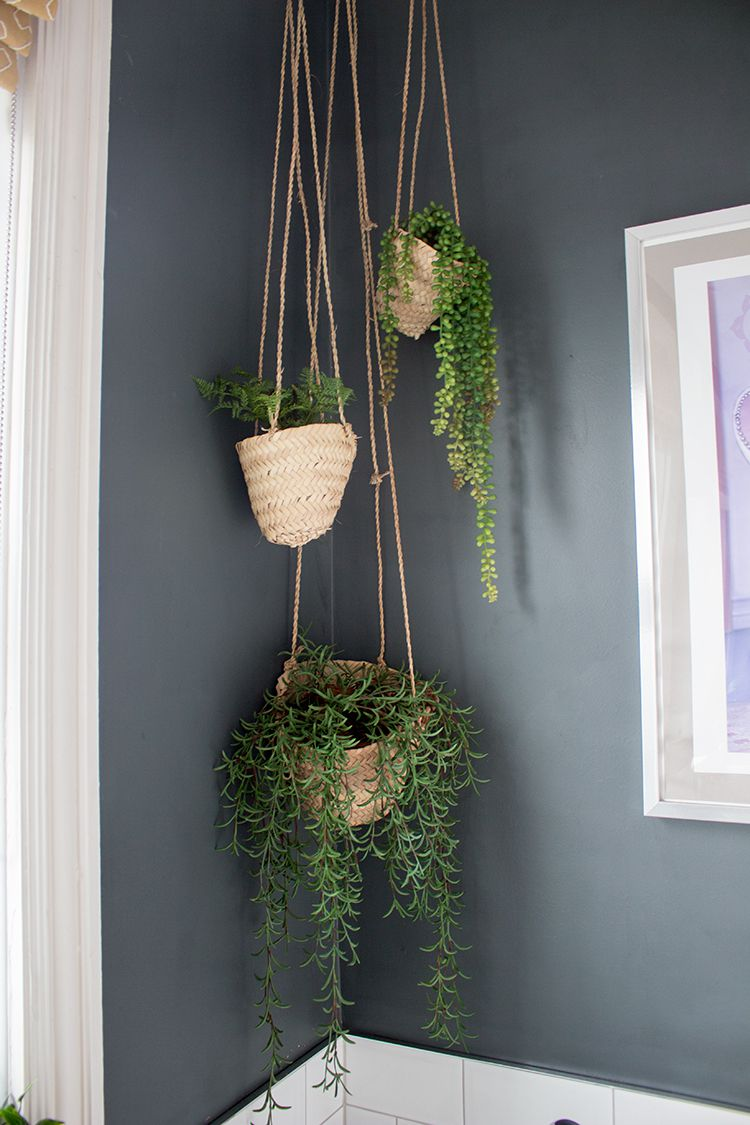 A close up photo of the three woven hanging planters with plants in them, hanging in the corner of the bathroom.