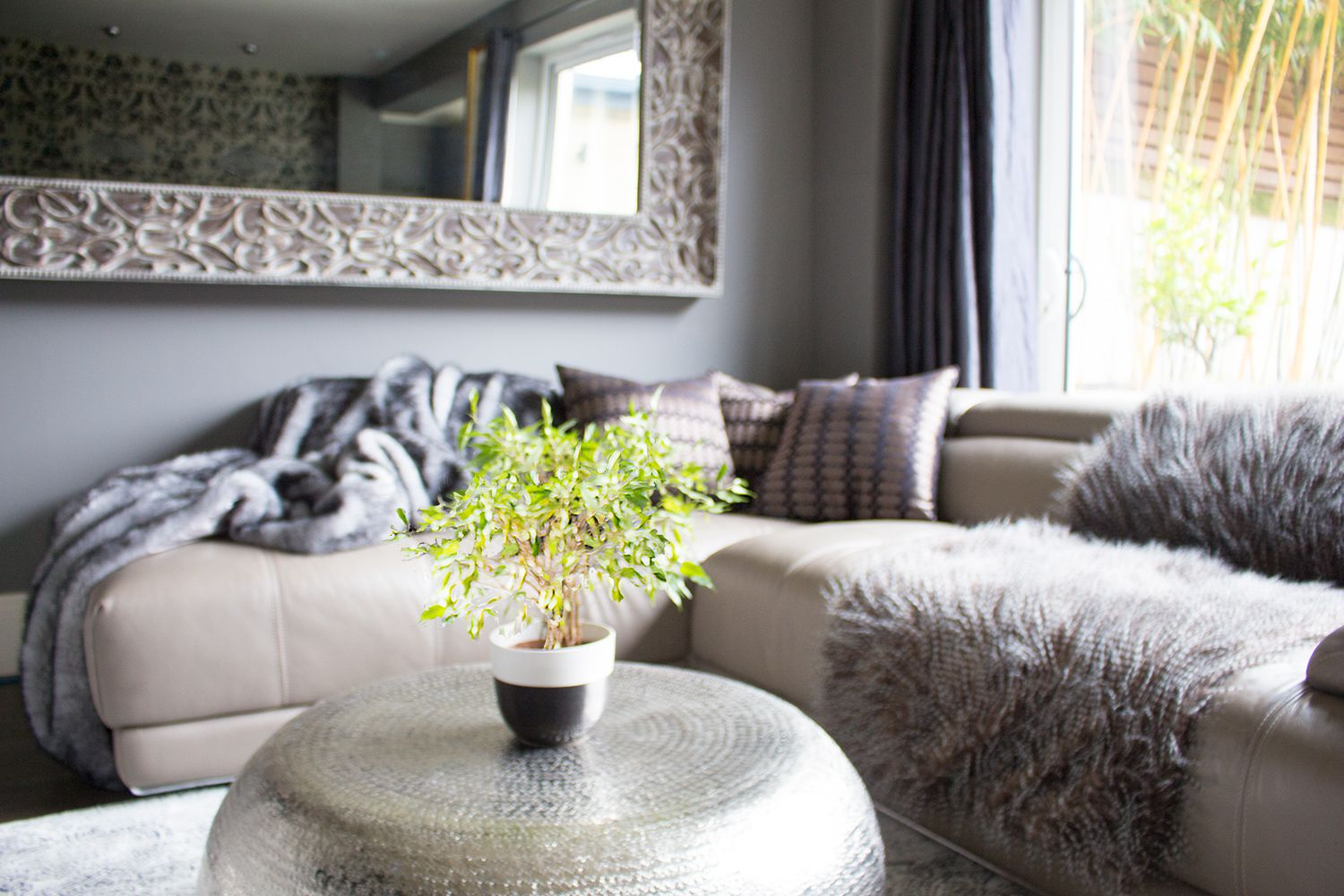 A photo of the hammered metal coffee table in the foreground, with the sofa, cushions and throws in the background.