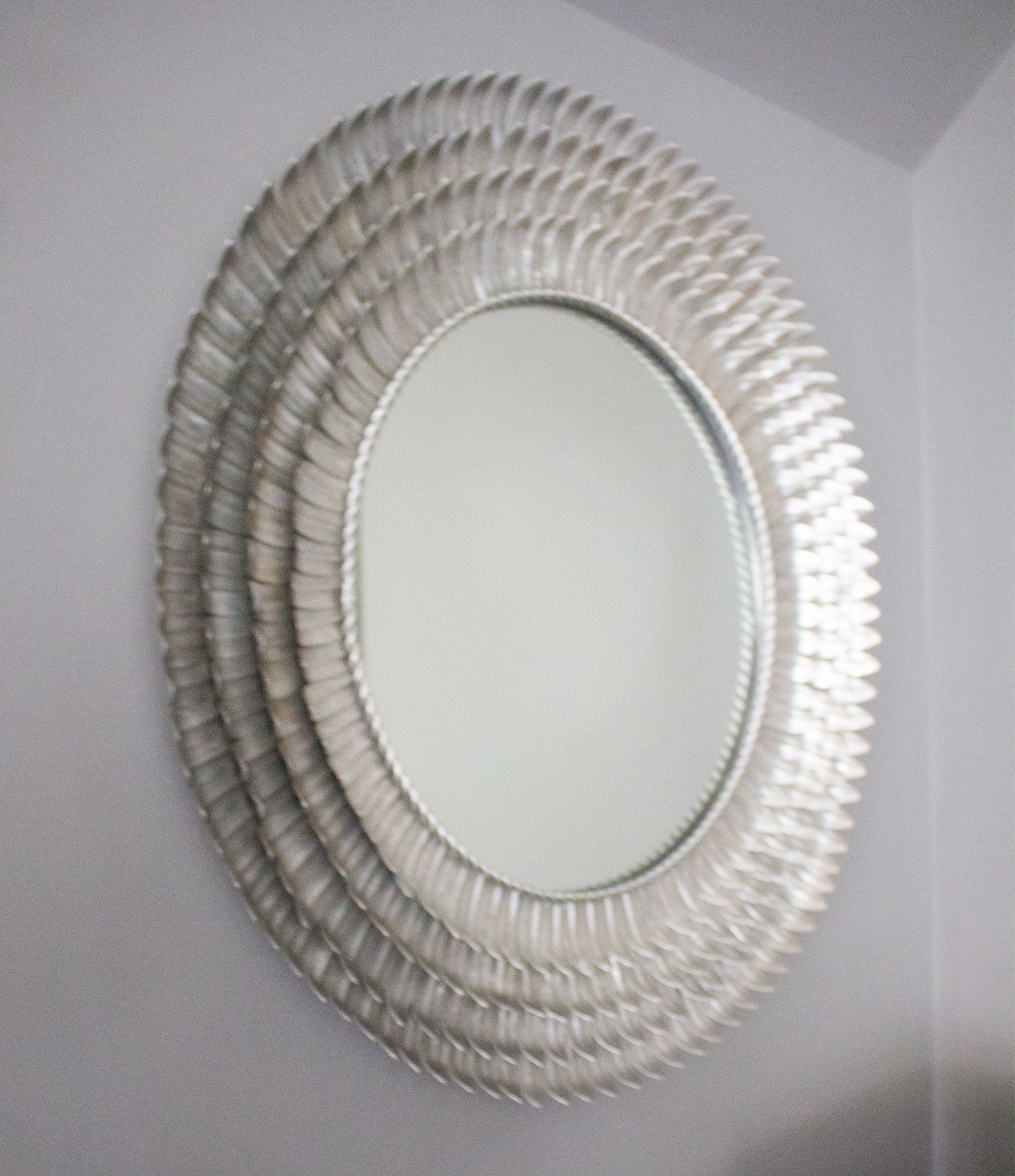A close up of the silver mirror, with a metal feathered frame.