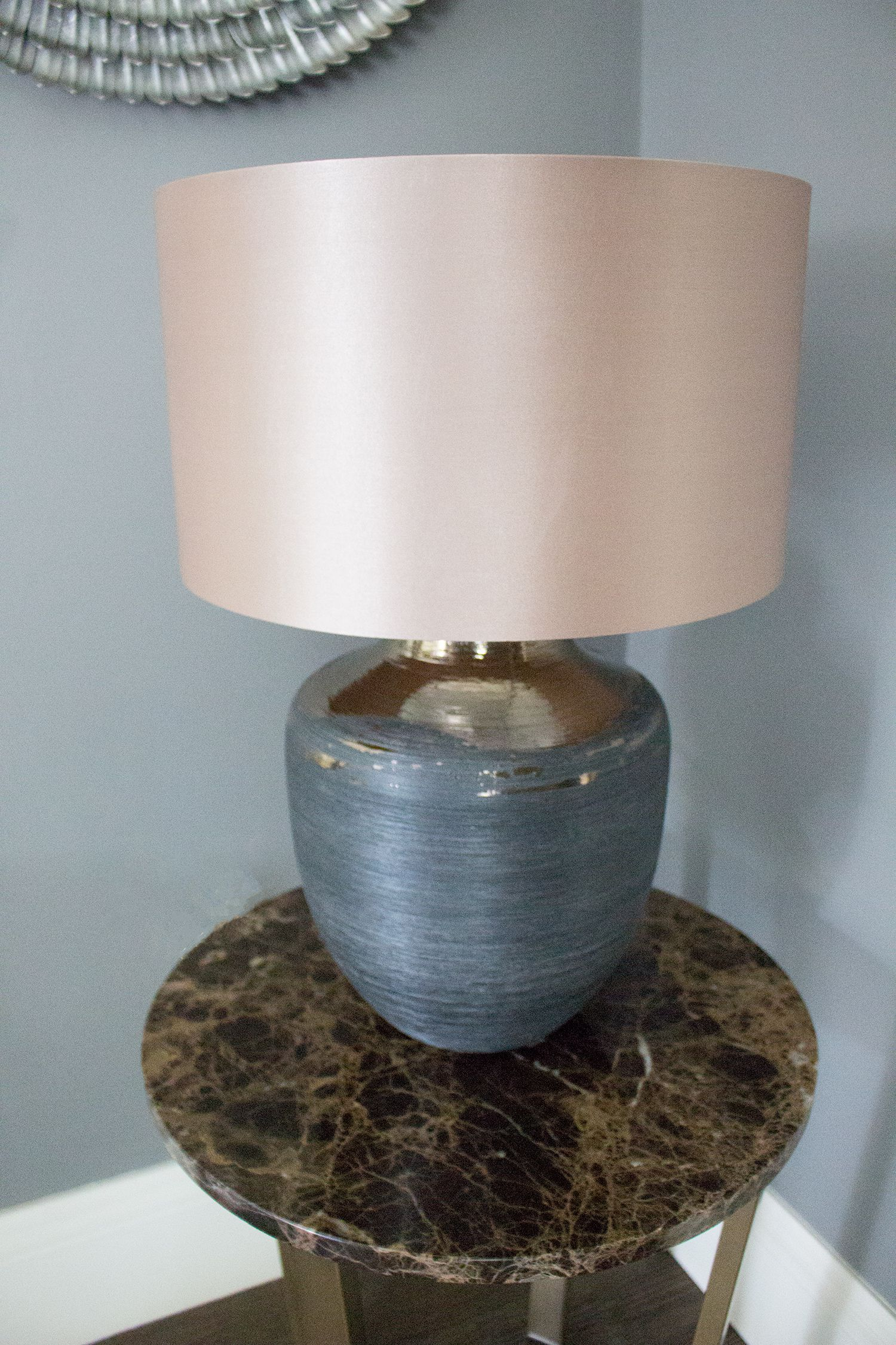 A close up of the new marble topped side table, with the black lamp base and grey satin lampshade.