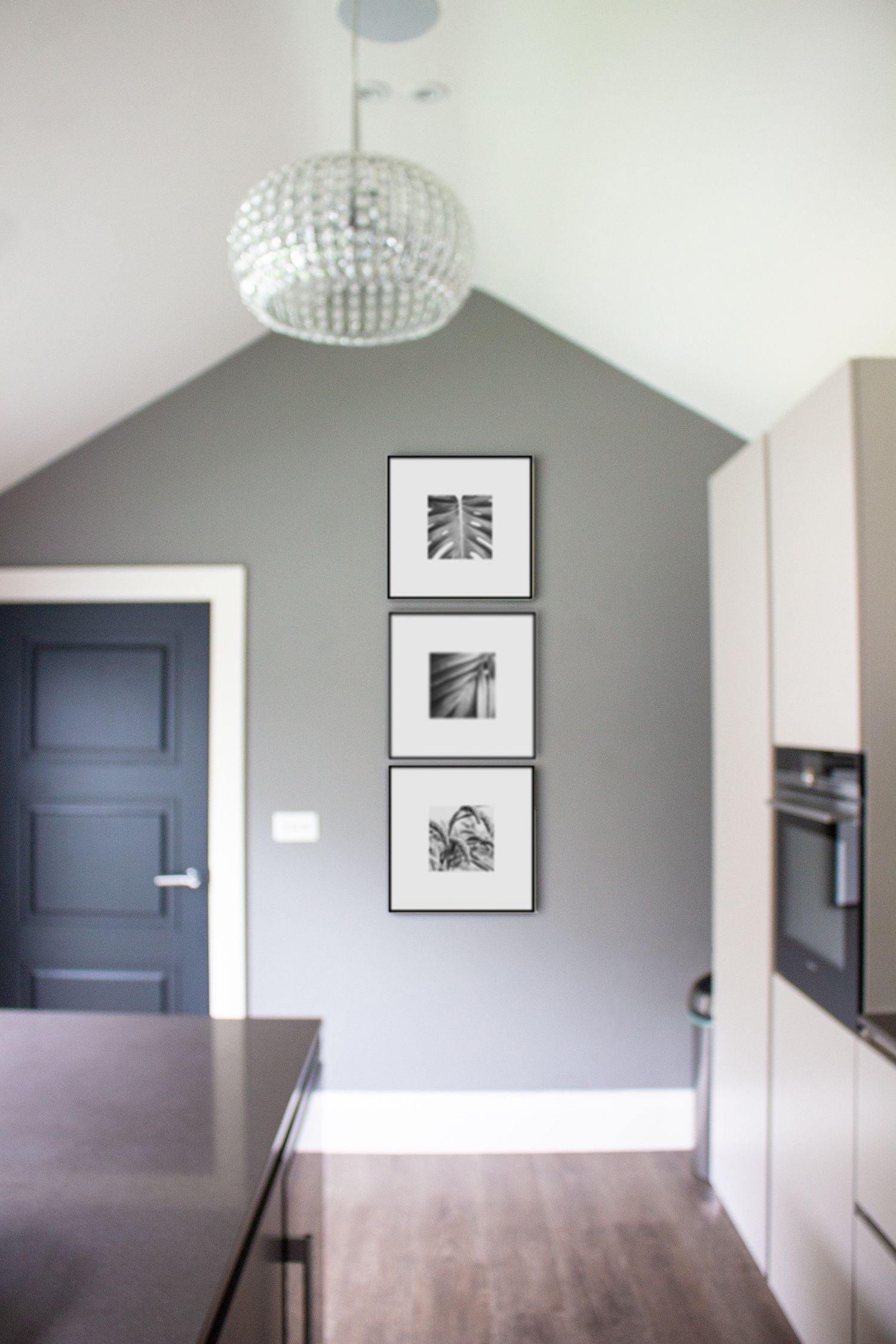 A photo of the three new black and white prints on the wall at the far end of the kitchen.