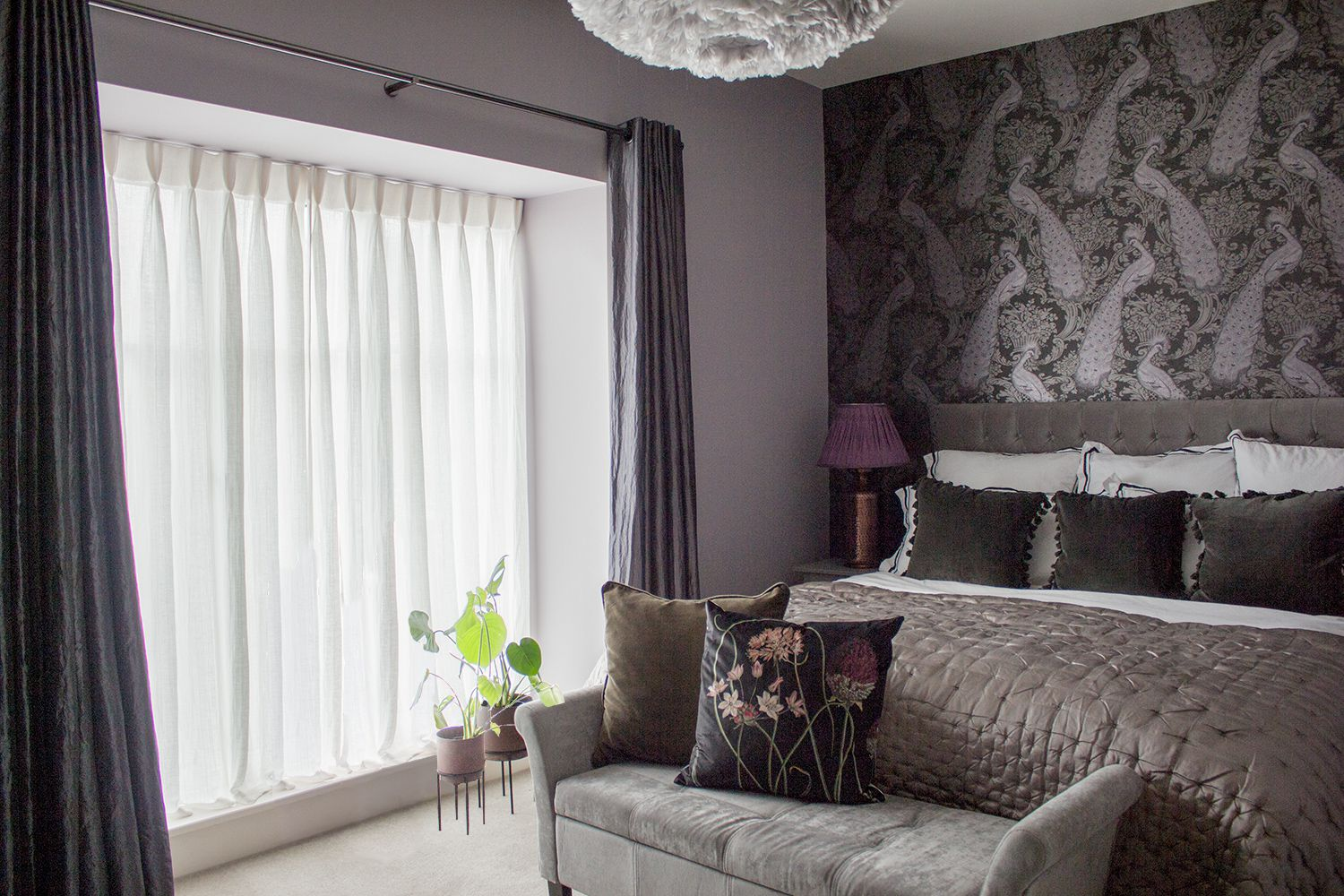 A view of the bed and peacock wallpaper behind. The windows have the original black curtains and sheer curtains added, and some plants in planters.
