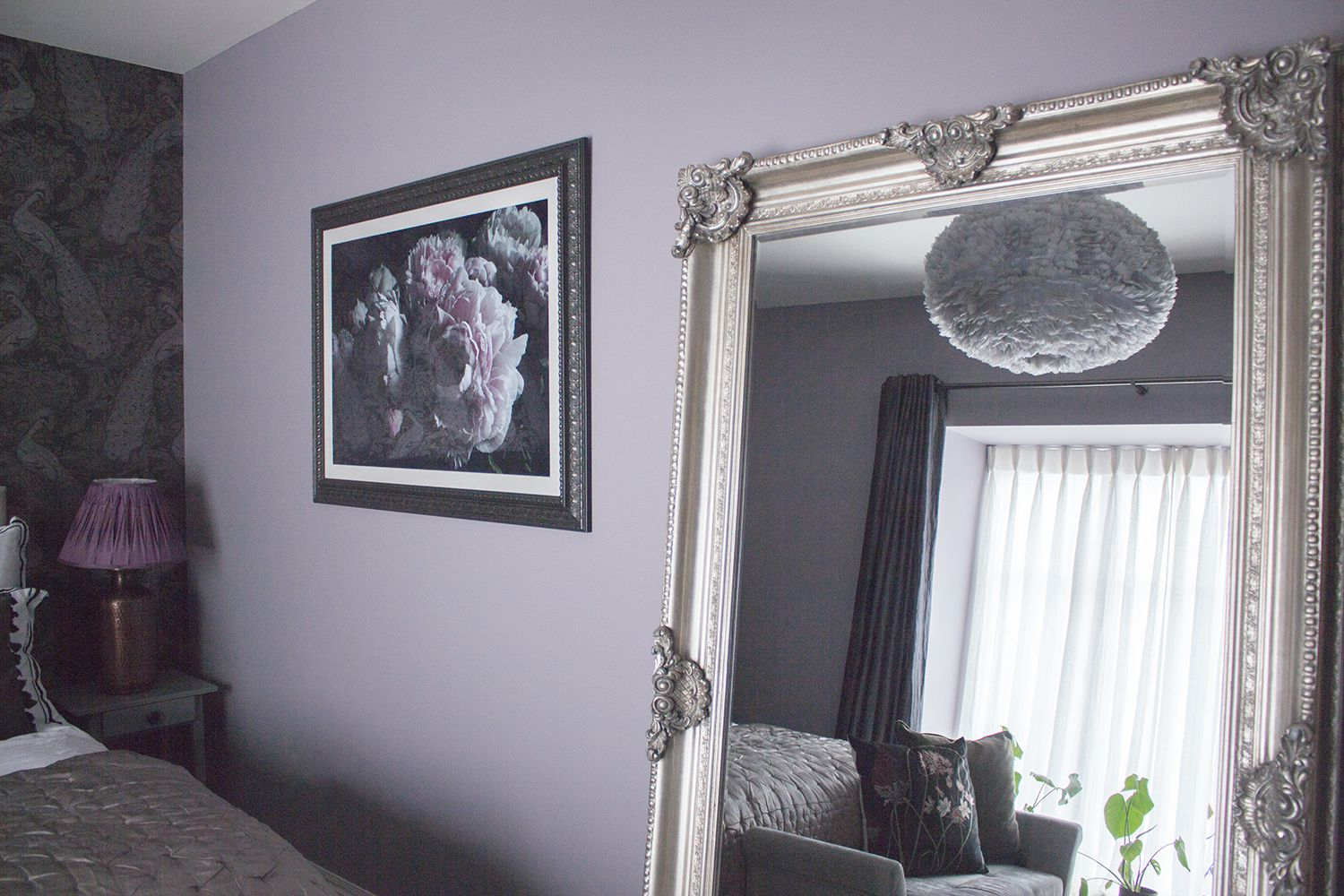 A photo of the ornate leaner mirror against the lilac wall, with the new purple and black floral artwork.