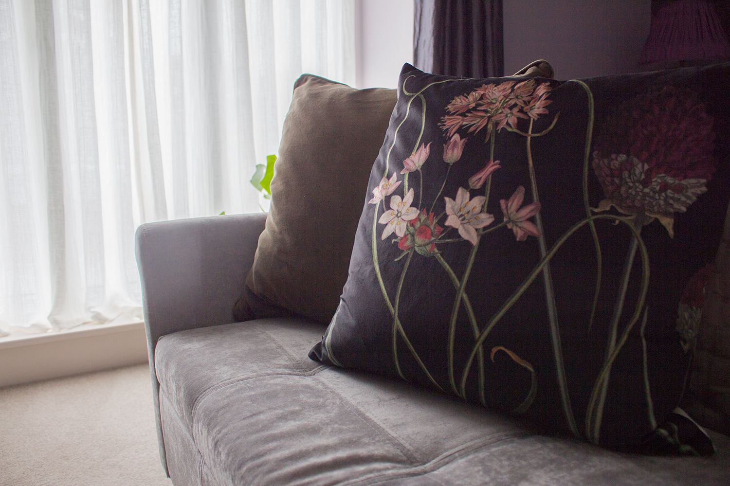 A close up of the new velvet cushions on the upholstered bench with the new sheer curtains behind.