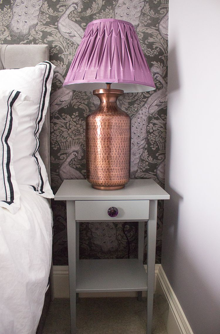 A photo of the new grey bedside table with a large copper lamp and purple pleated shade.