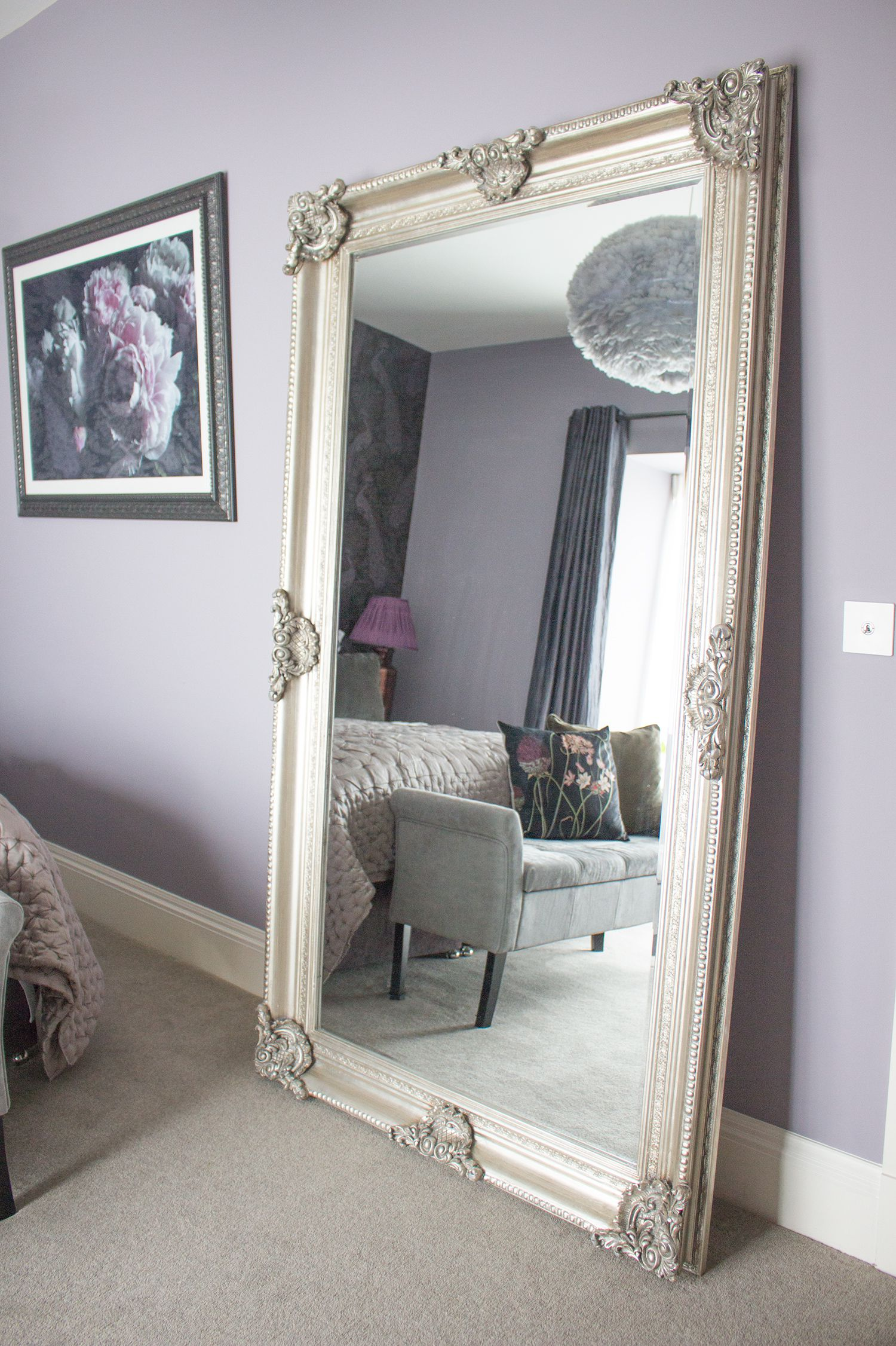 A photo of the large ornate silver floor standing mirror against the lilac walls.
