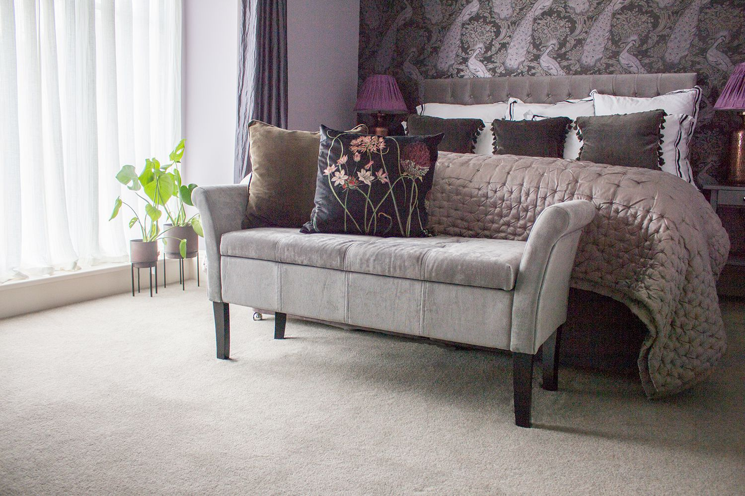 A view of the bed with the silk bedspread, and the grey velvet upholstered bench in front.