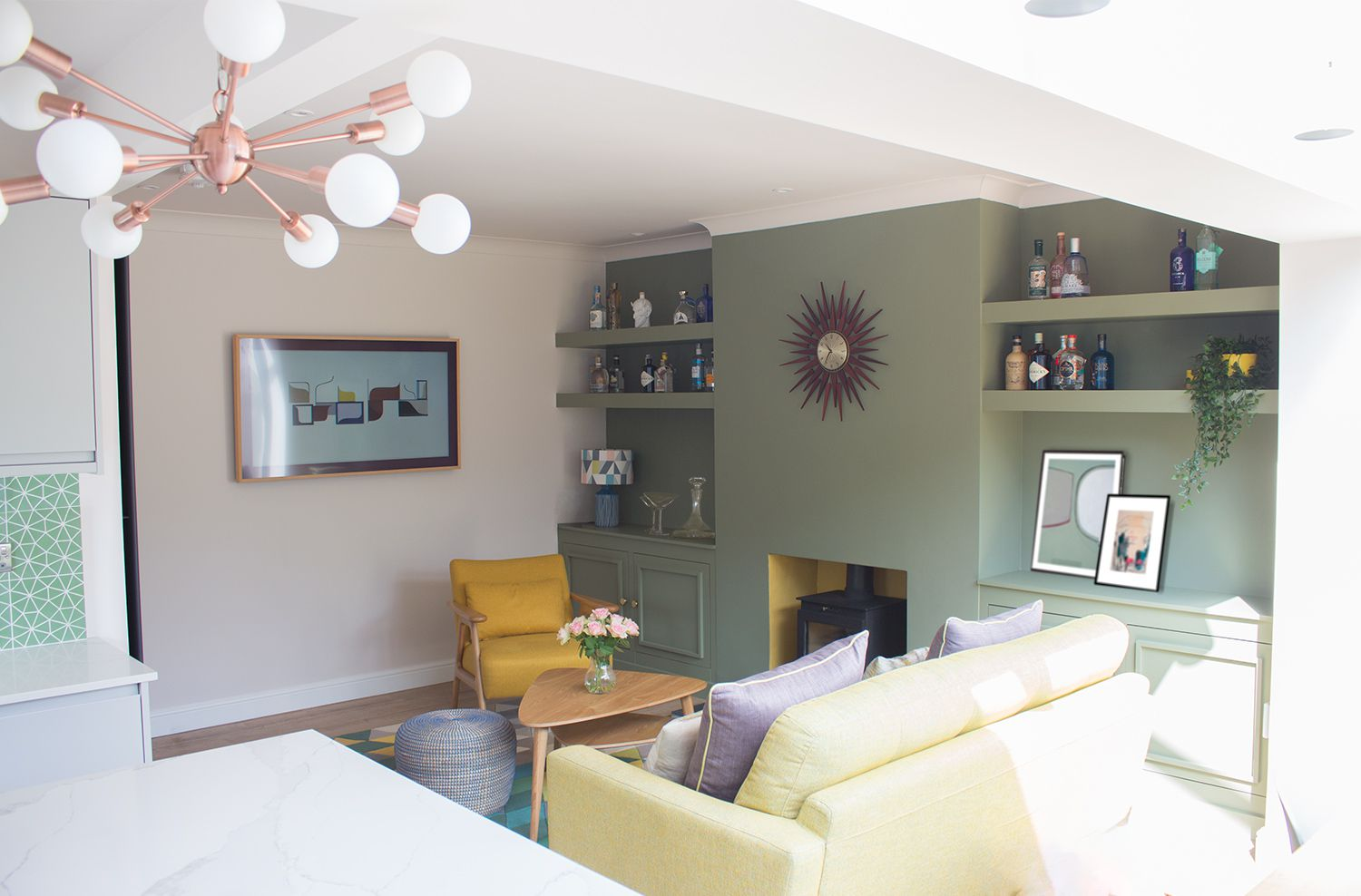 A view of the green painted built in shelving, with the Frame TV on the wall, and the sofa and yellow armchair.
