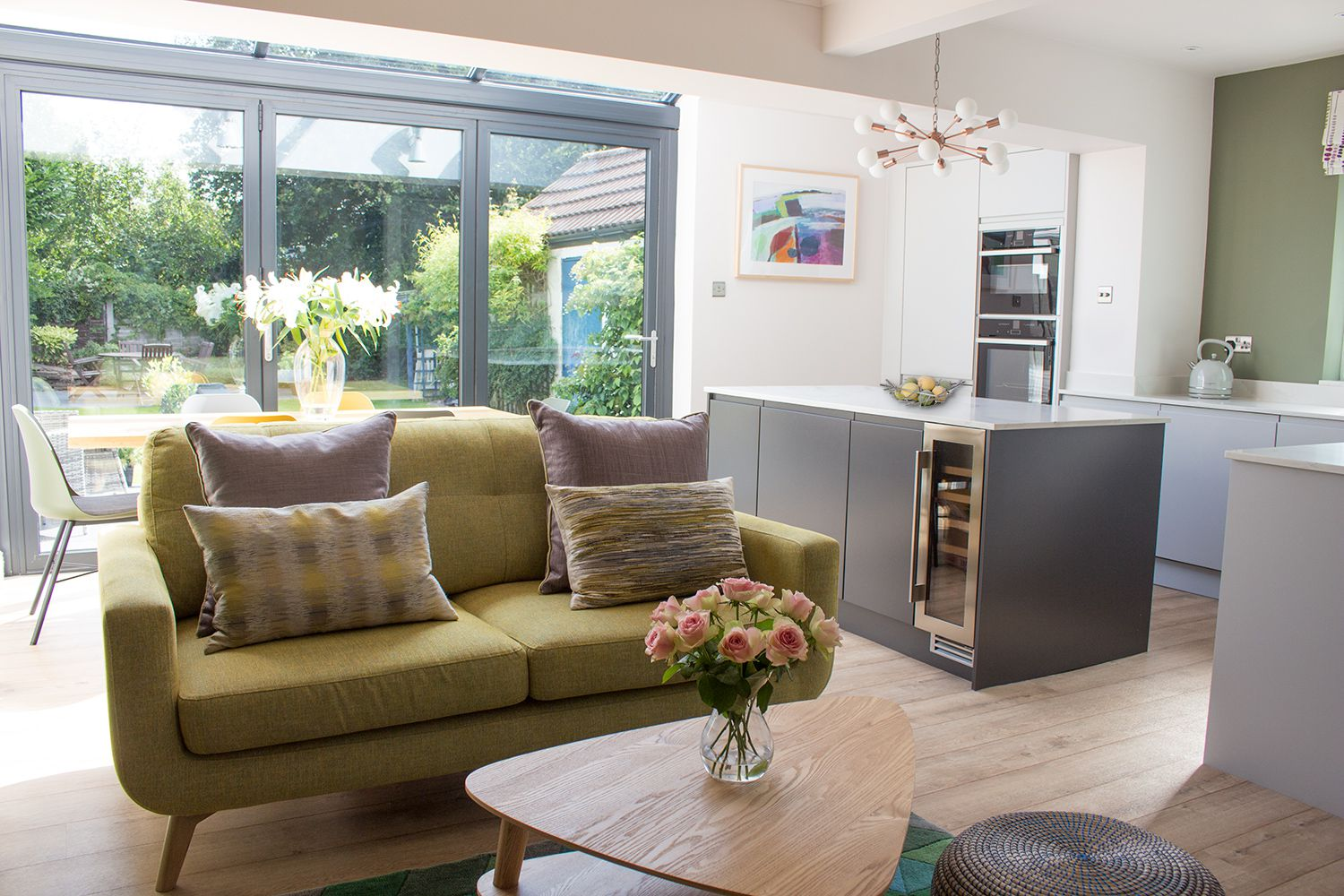 A photo of the pale green sofa, oak coffee table and the kitchen area and dining table behind.