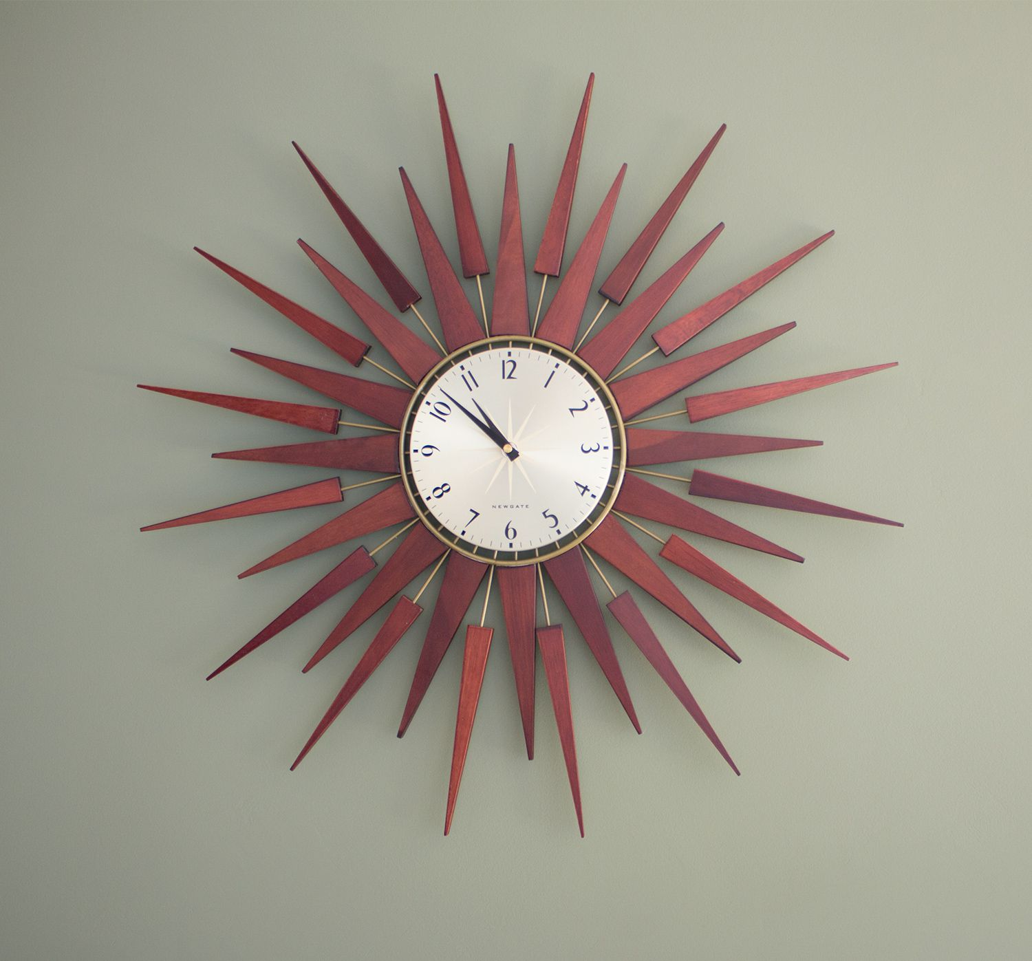 A close up of the walnut sunburst clock on the wall.