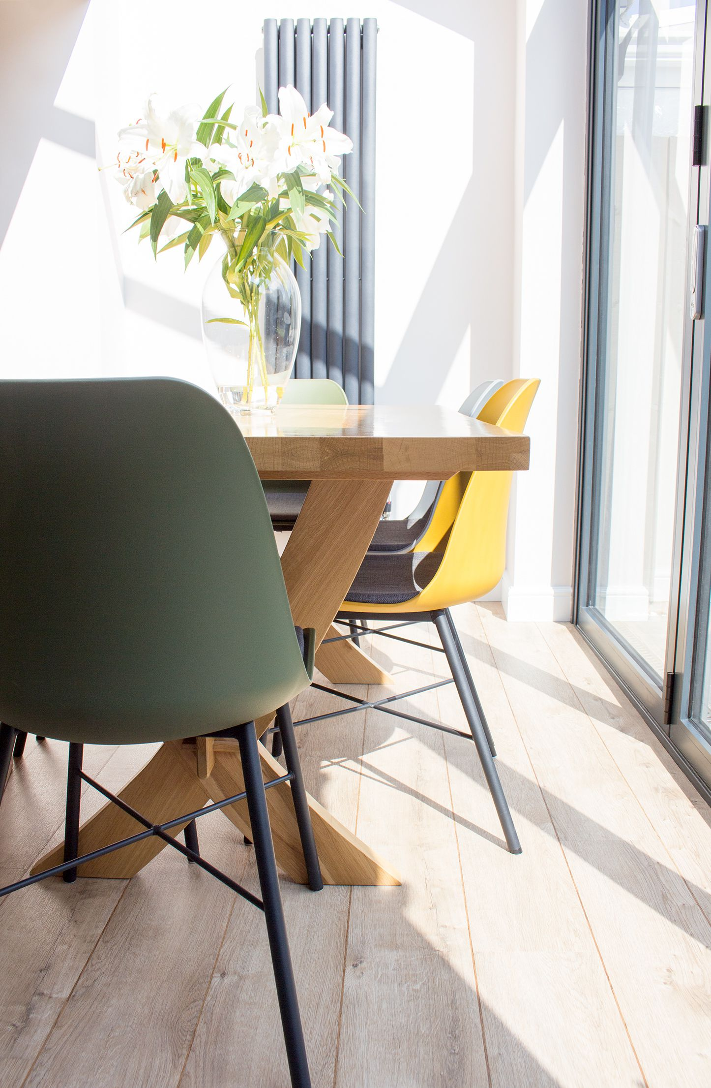 A photo of the new light oak flooring, the dining table and the yellow, green and grey dining chairs.