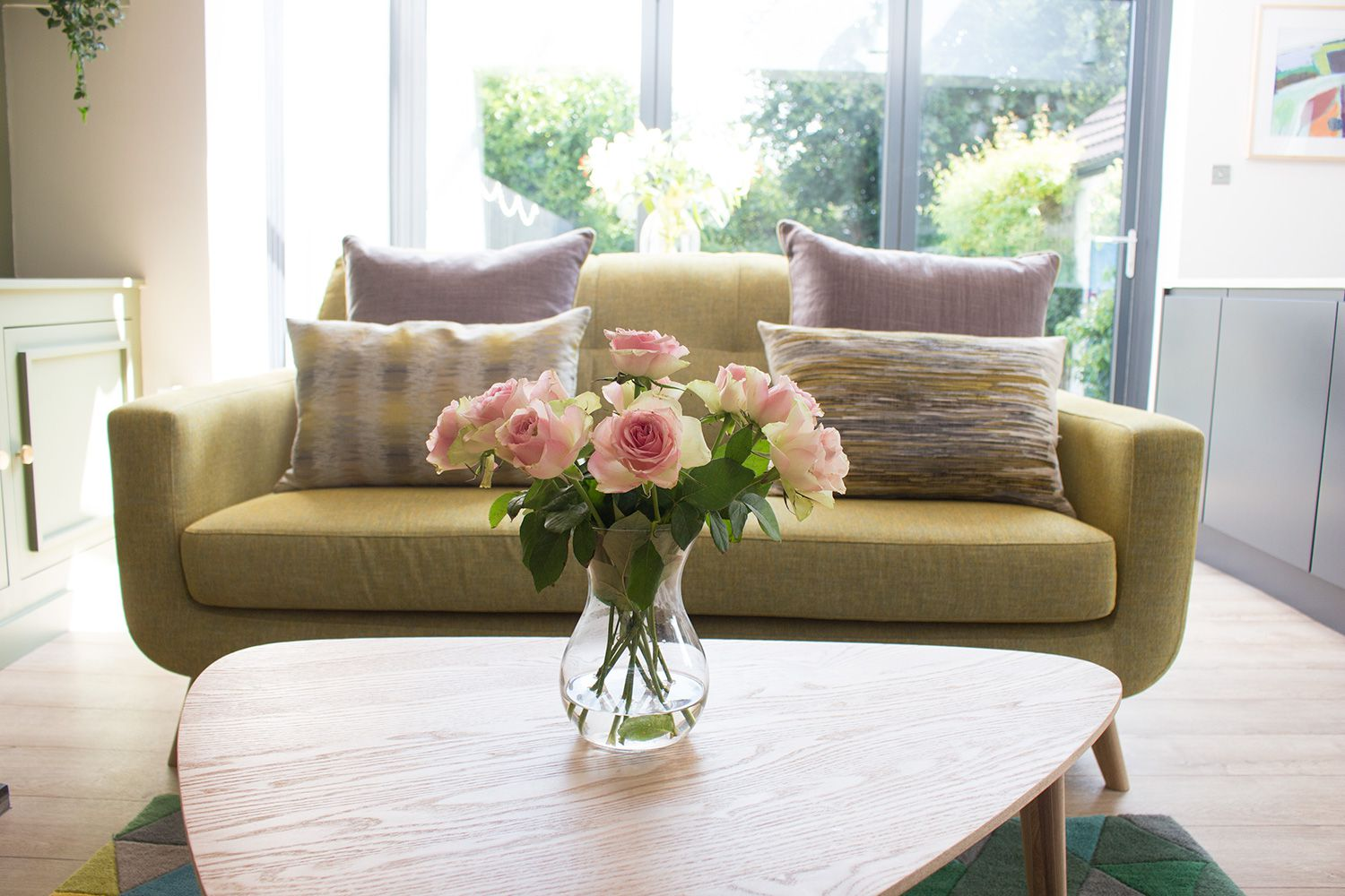 A view of the pale green sofa with the oak coffee table and fresh flowers in front.