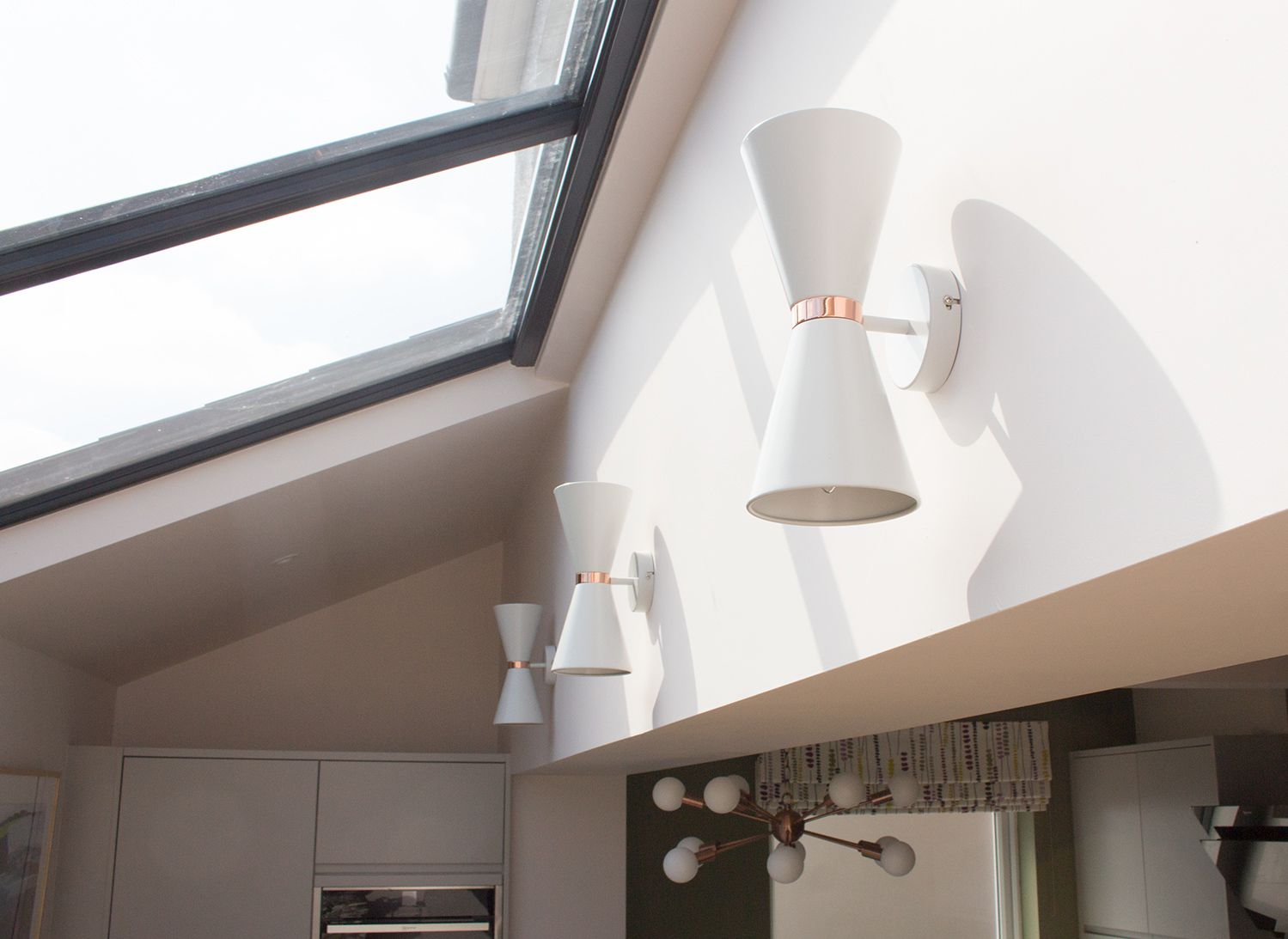 A photo of the three wall lights in the extension area, with the glass roof above.