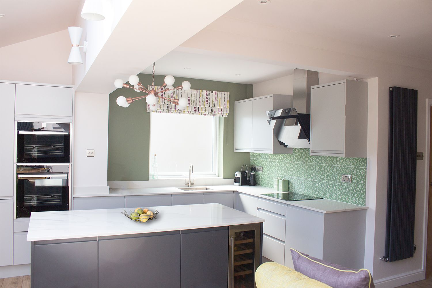 A photo of the kitchen area with light grey cabinets, marble worktops and a funky green geometric tile for the splashback.