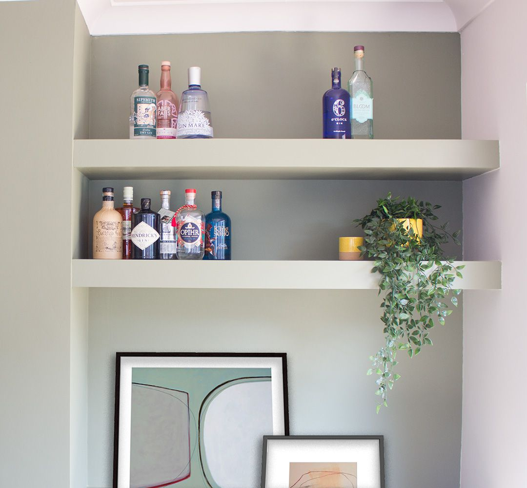 A close up of the built in shelves styled with gin bottles, a plant and artwork.