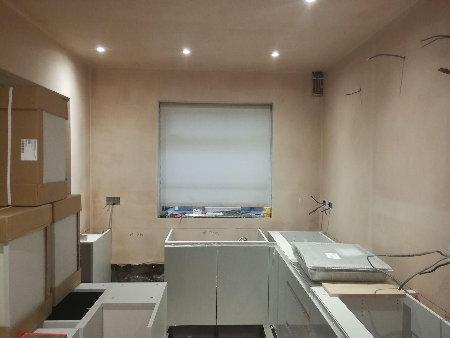 A photo of the kitchen area with the old window, bare plaster walls and no window dressing.