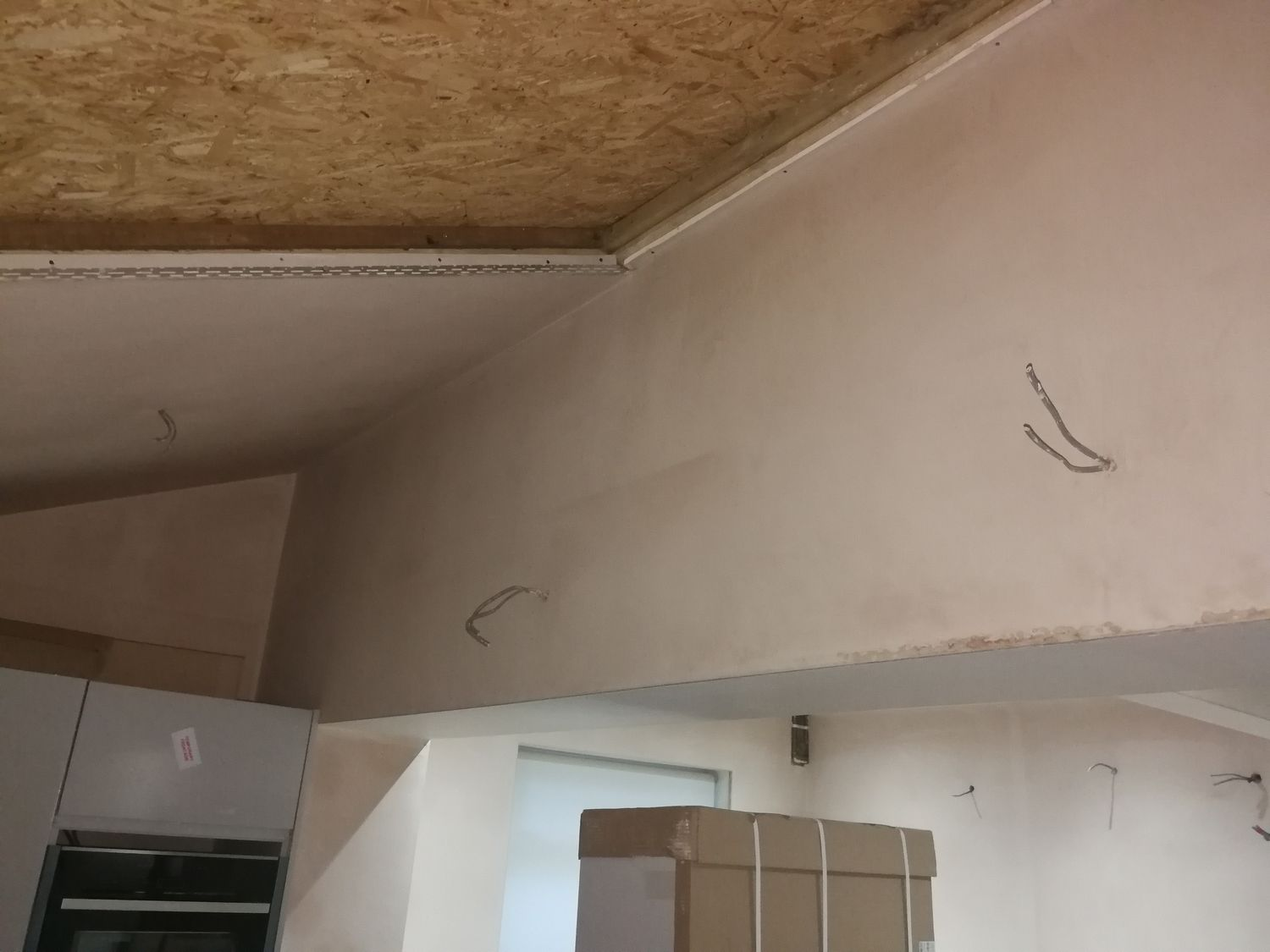 A photo of the same angle with bare plaster walls and chipboard covering where the glass roof will go.