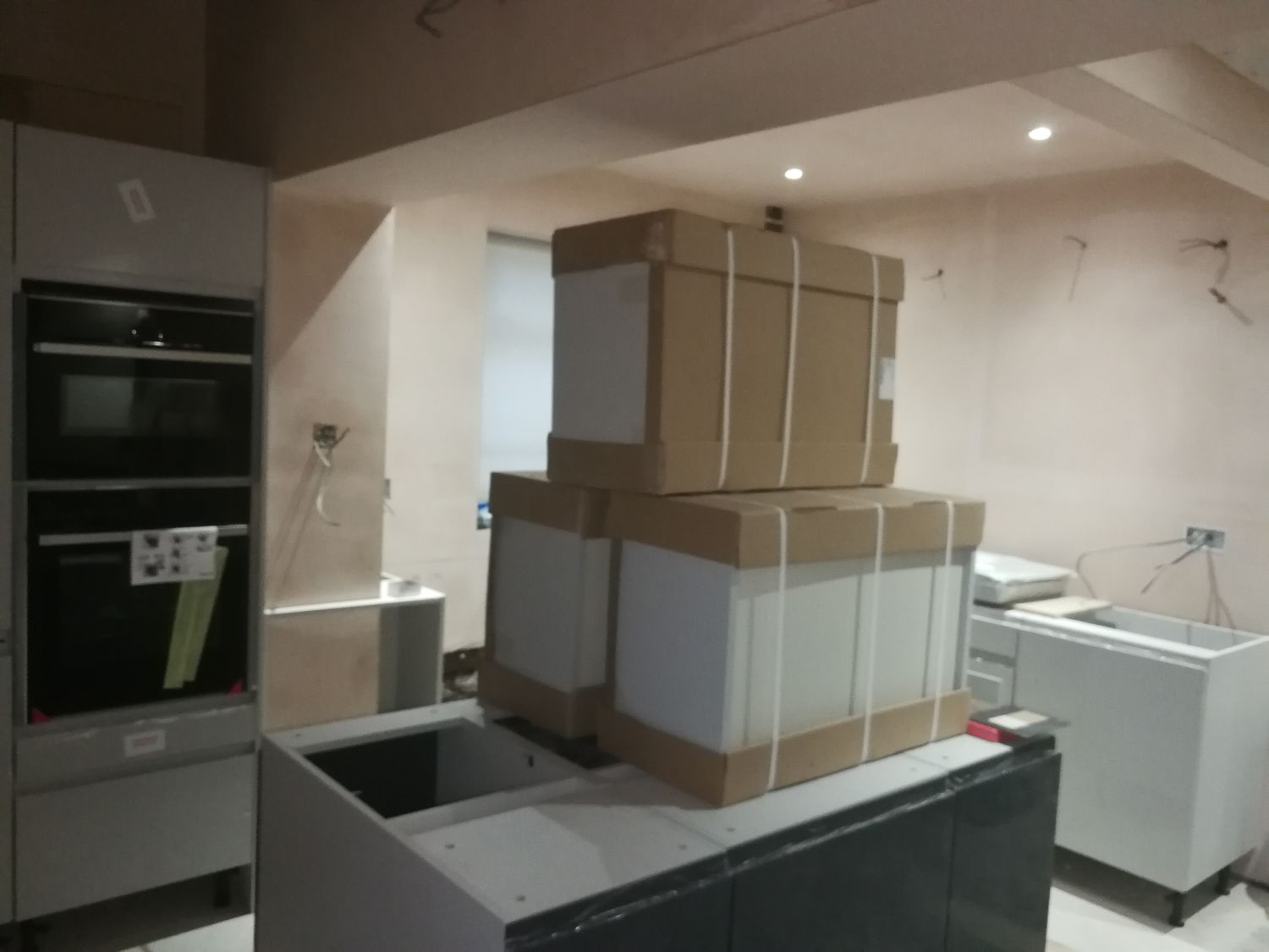 A photo of the same angle of the kitchen area with the units partially installed and bare plaster walls.