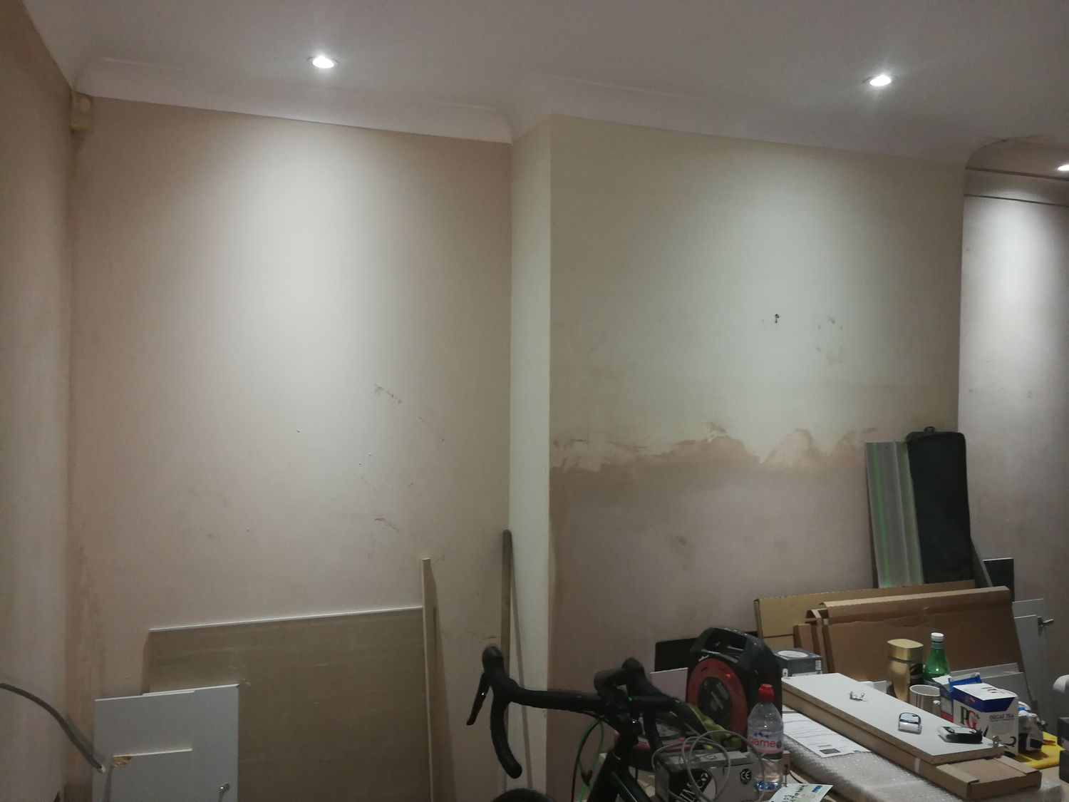 A photo of the same angle with bare plaster walls, and before the wood burning stove was installed.