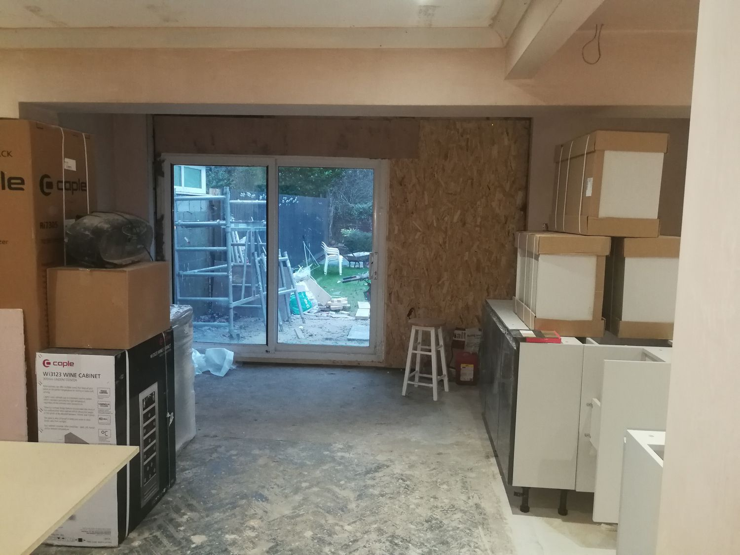 A photo of the same angle with bare plaster walls, some of the kitchen units stacked up and temporary uPVC sliding doors.