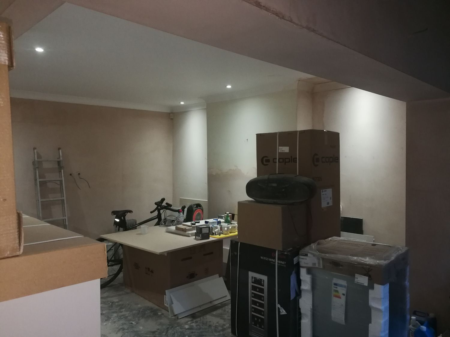 A photo of the same angle before the shelving was built, with bare plaster walls and some of the kitchen units stacked up.