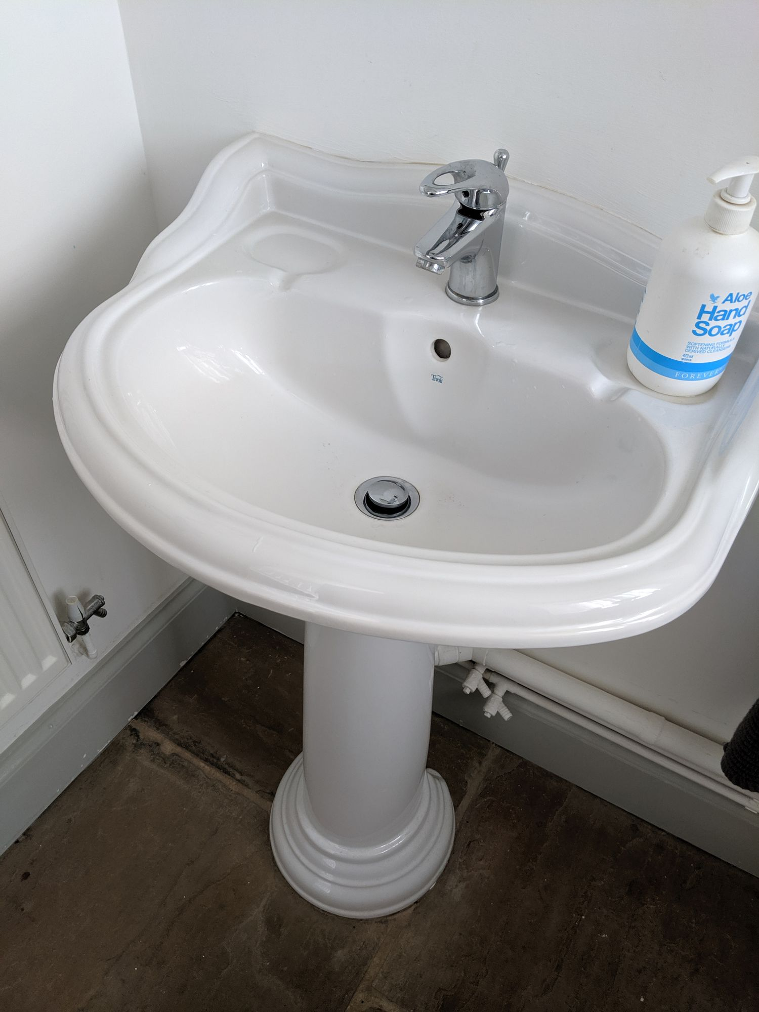 The overlarge pedestal sink before the room was changed.