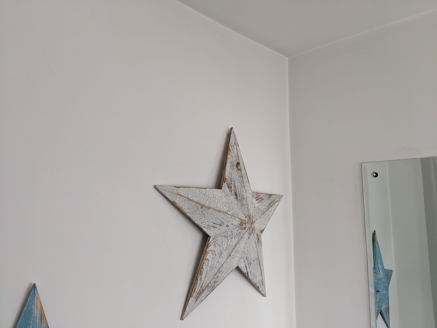 A photo of the area before, which had a plain mirror and a big star on the wall.