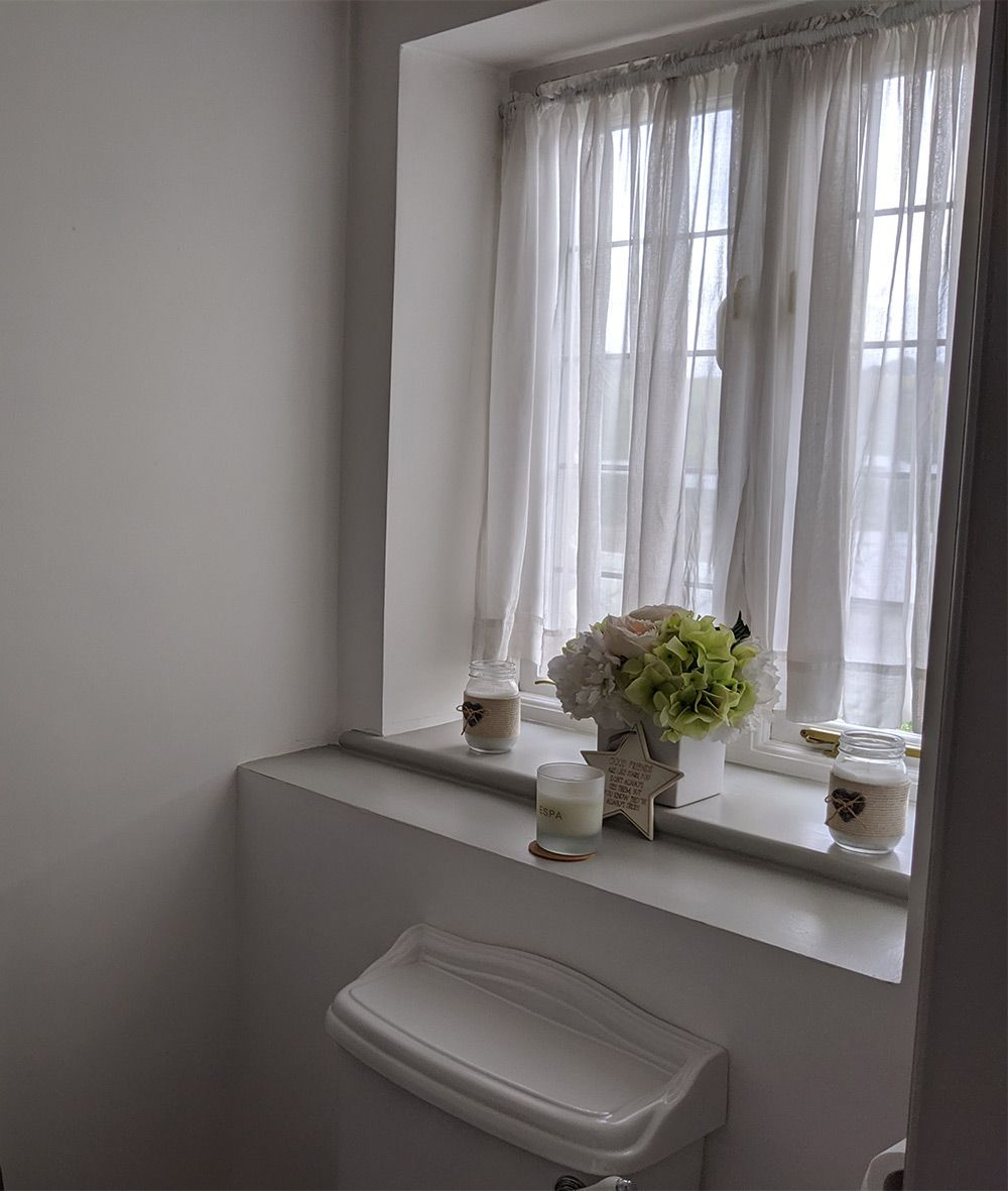 A photo of the loo before, with net curtains and a traditional style WC.