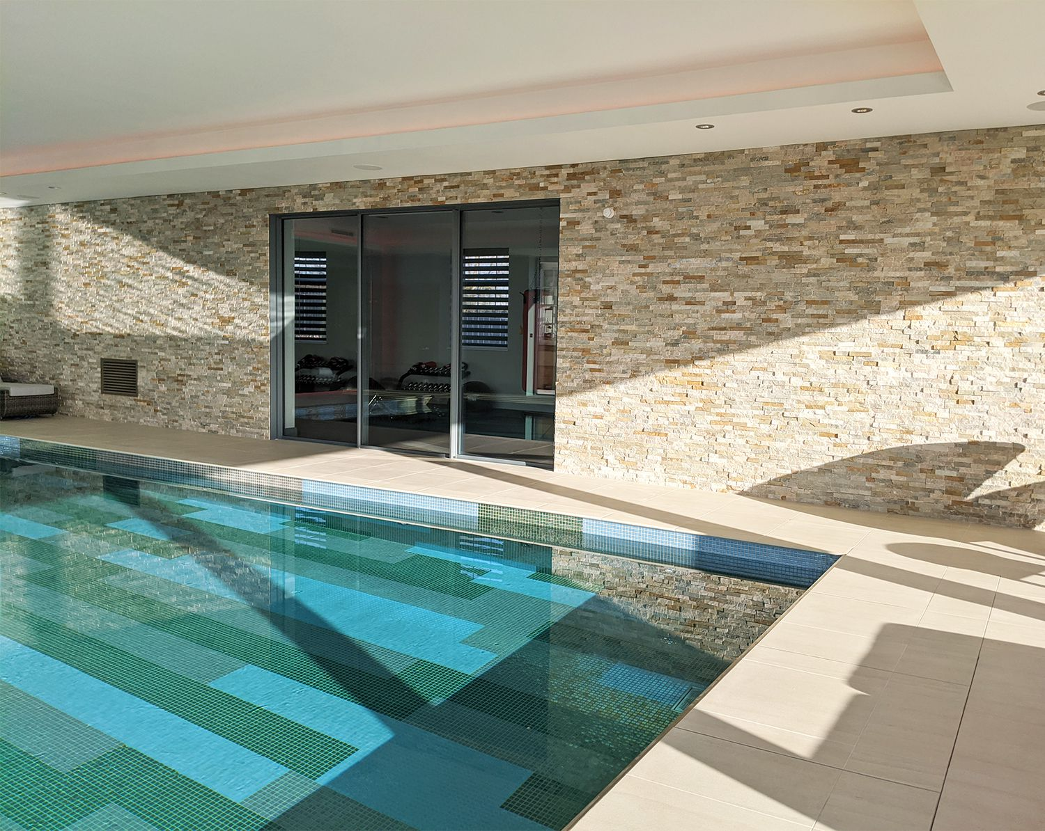 The pool with the glass doors which are the entrance to the gym.