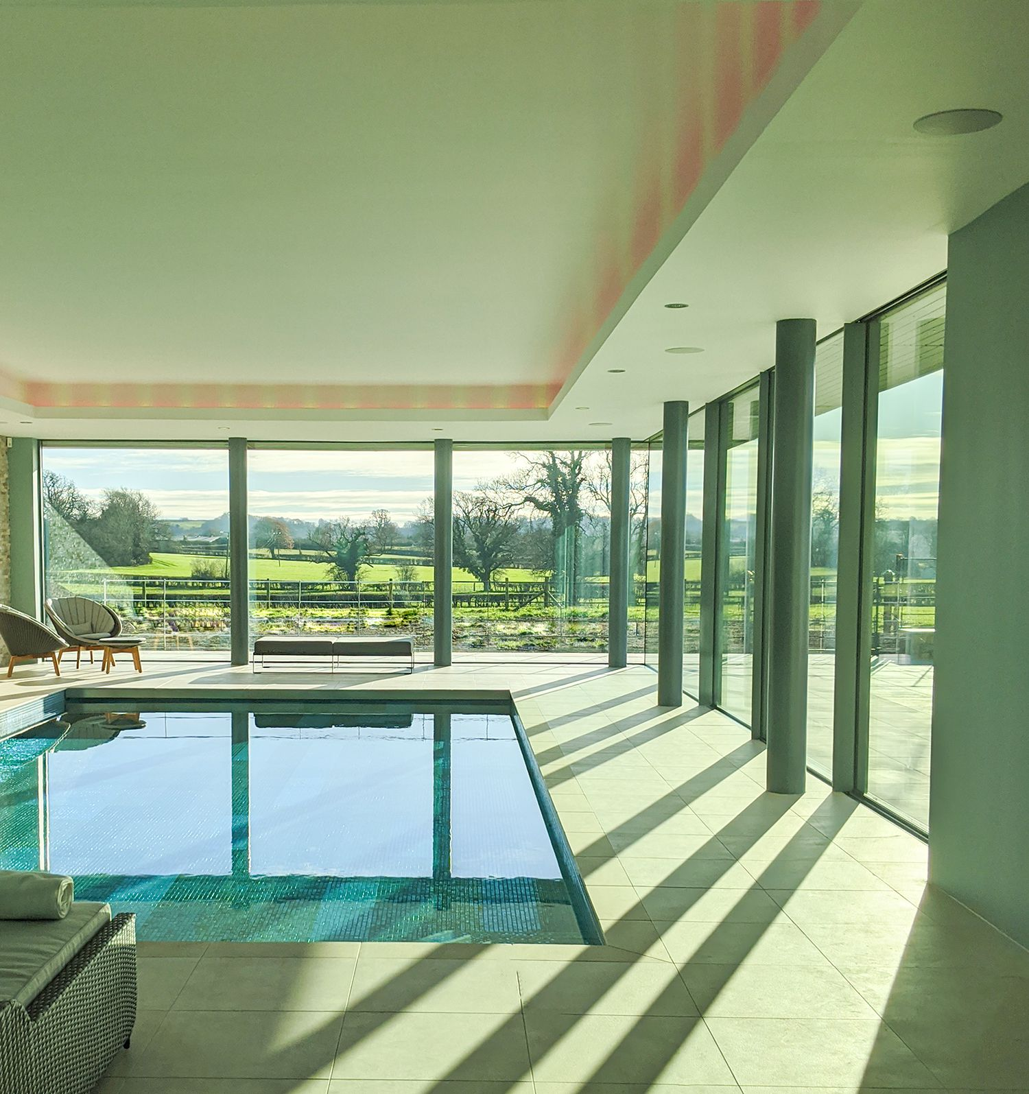 A photo looking down the length of the pool, with the sun streaming in through the glazing.