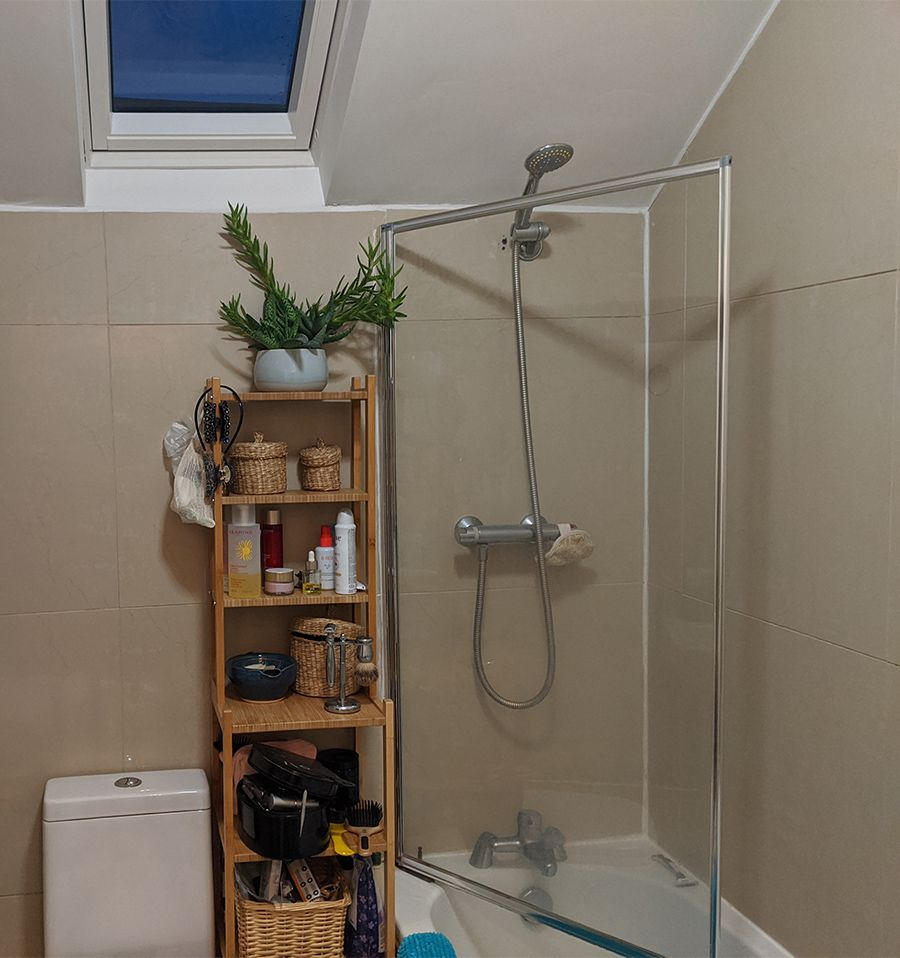 The old shower with a small shower head and dirty shower screen.