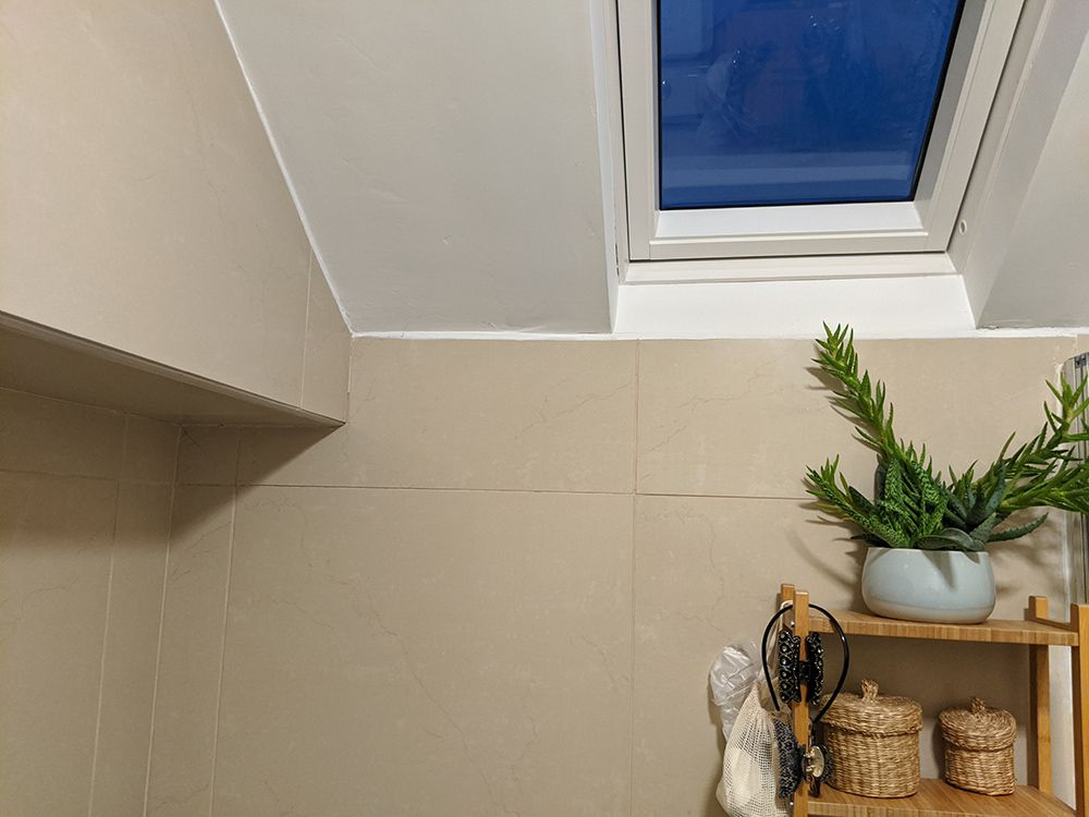 A photo of where the sink recess is, with the beige tiles and old shelving unit.