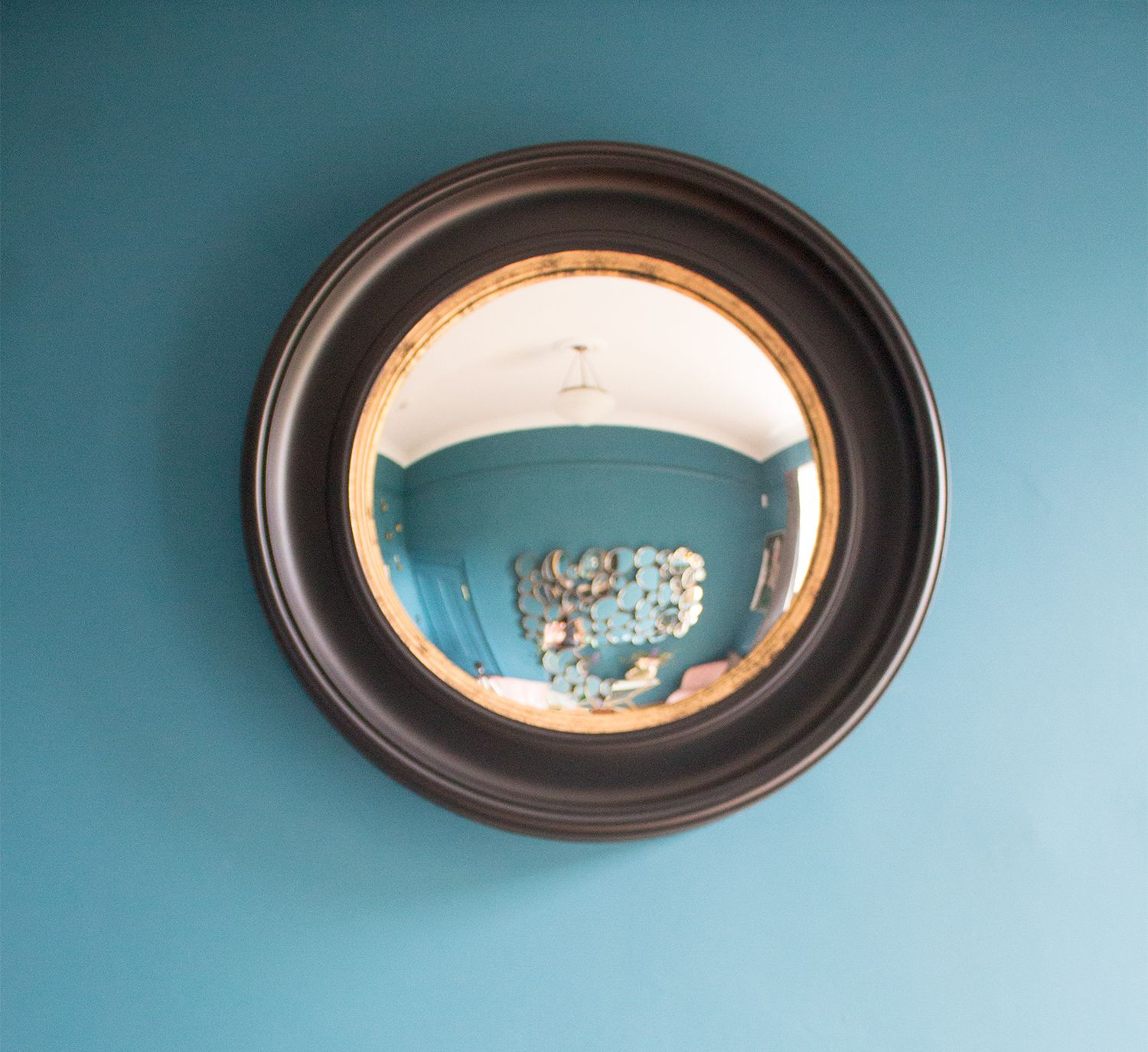 A close up photo of the black round mirror in the teal painted room.