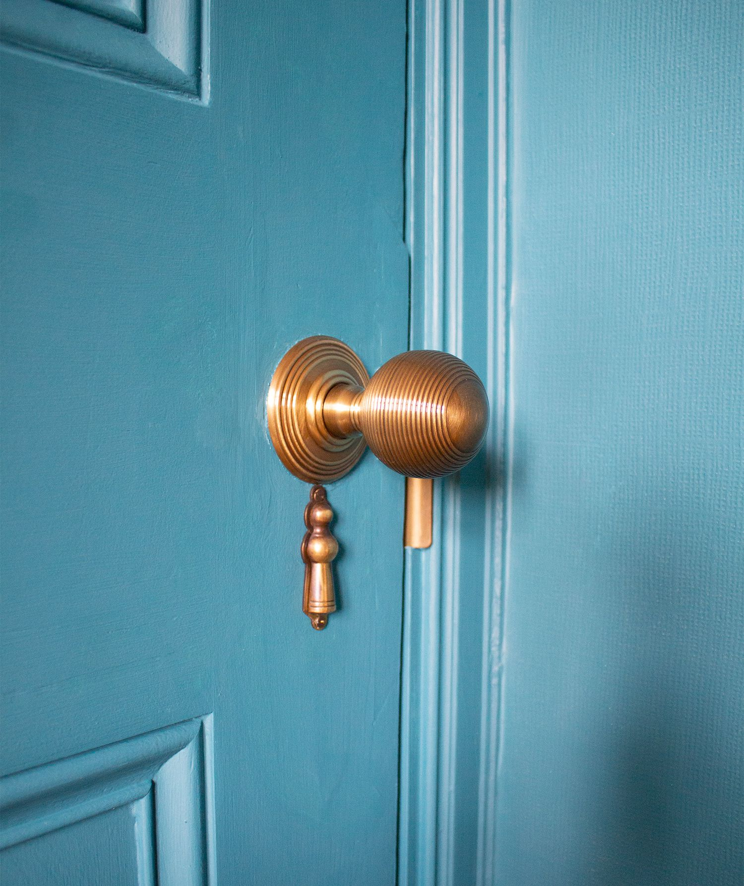 A close up of the new brass door handle in the teal painted room.