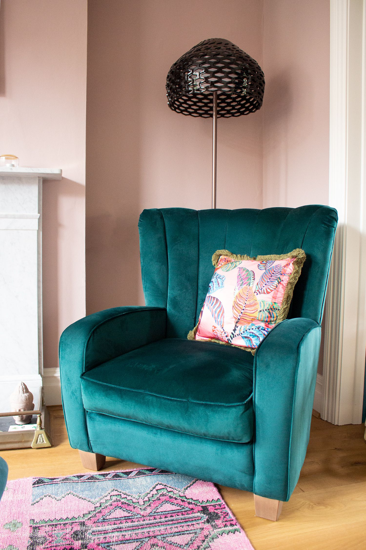 A close up photo of the green velvet armchair in the pink painted room, with a black floor lamp behind it.