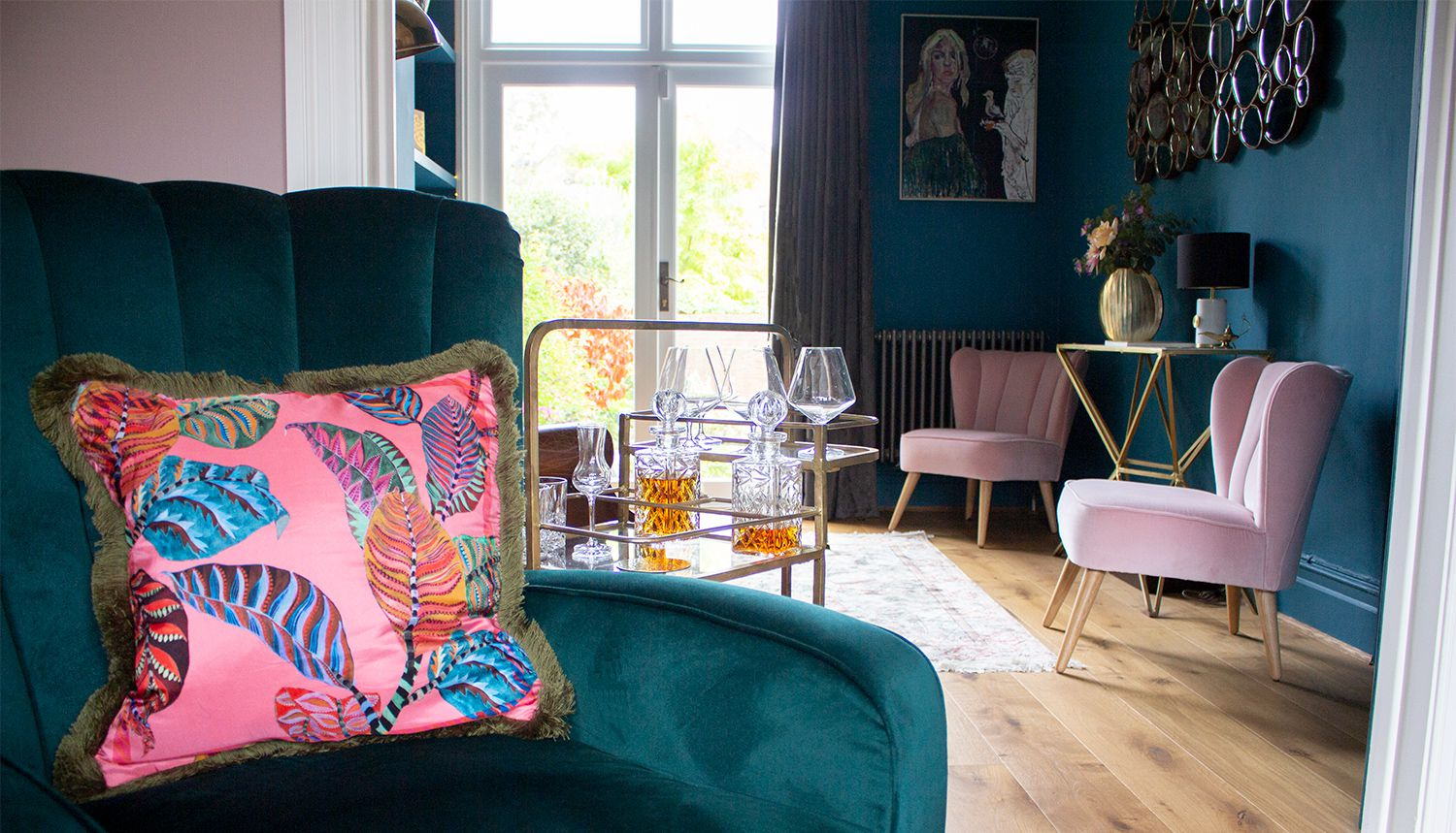 A view into the teal painted room, looking past the green velvet armchair with a pink cushion on it.