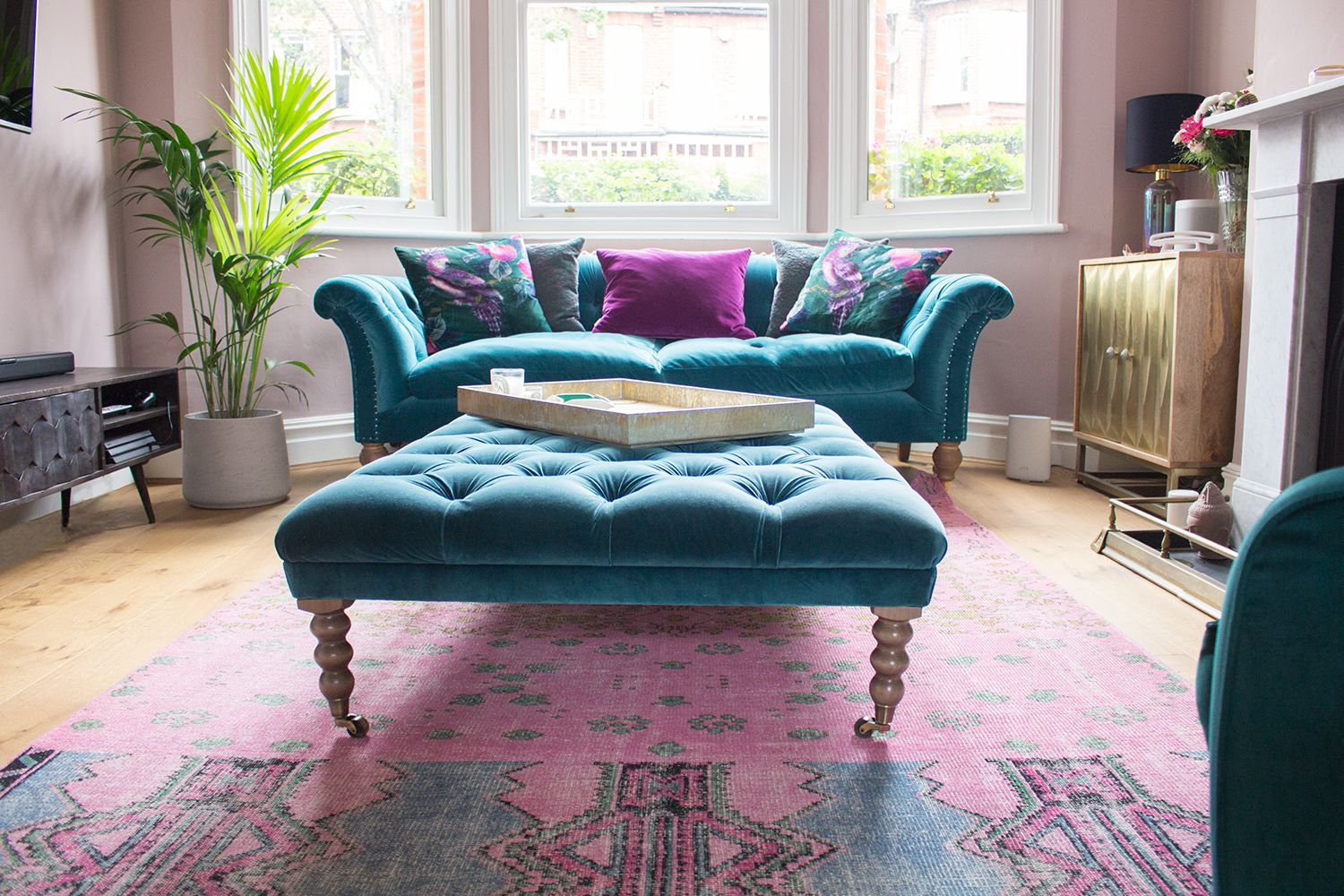 A photo of the teal velvet sofa, with the teal footstool in front, on a pink rug.