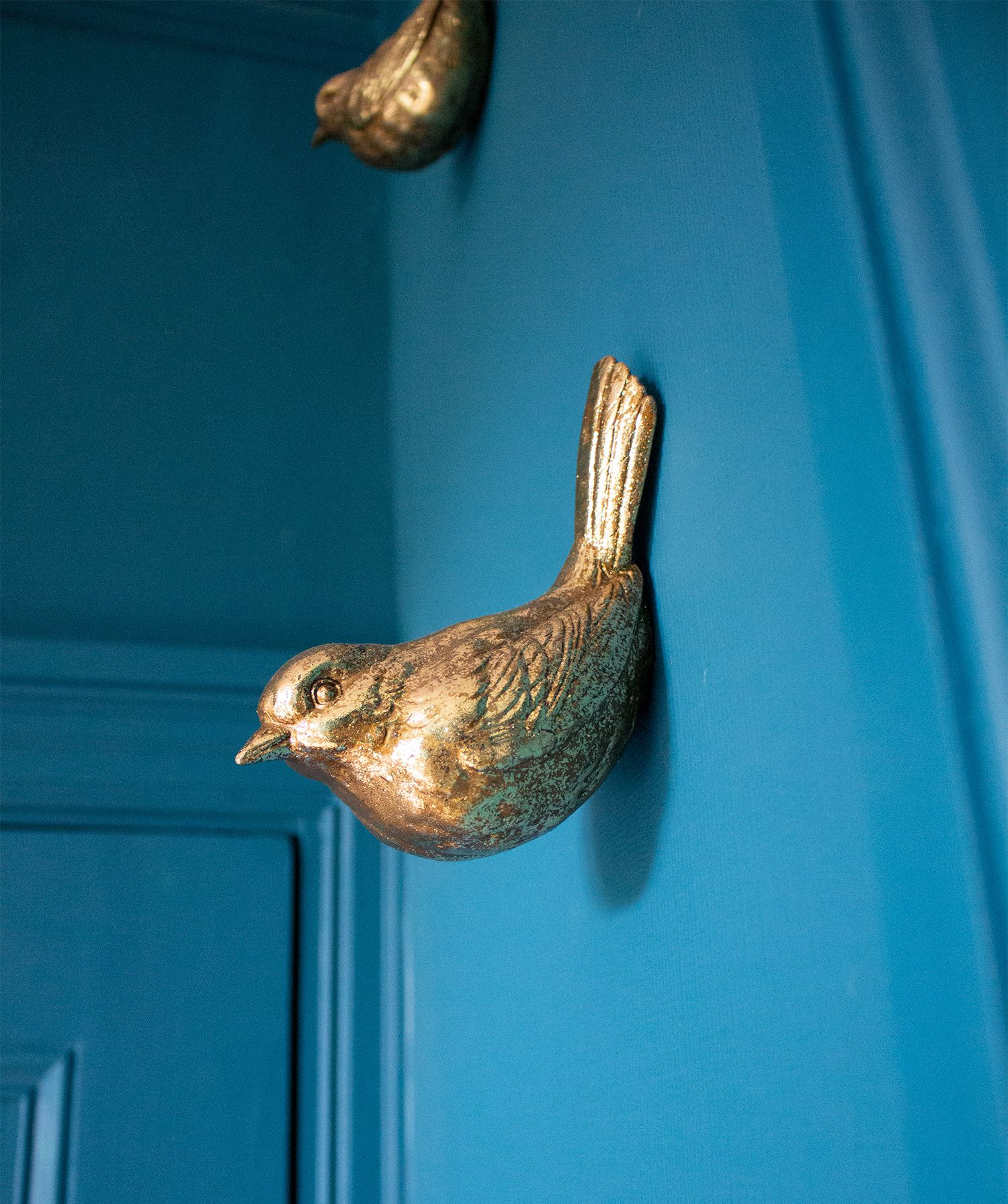 A close up photo of some brass decorative birds on the wall in the teal room.
