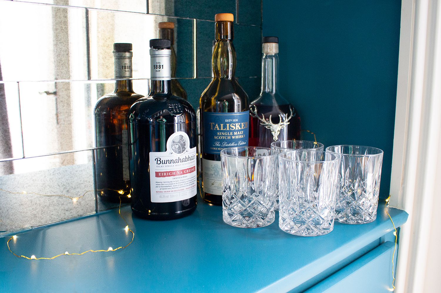 A close up photo of the spirit bottles and glasses in the teal painted room.
