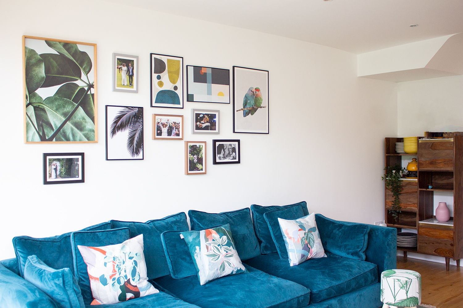 An view of the teal velvet sofa and the gallery wall at an angle.