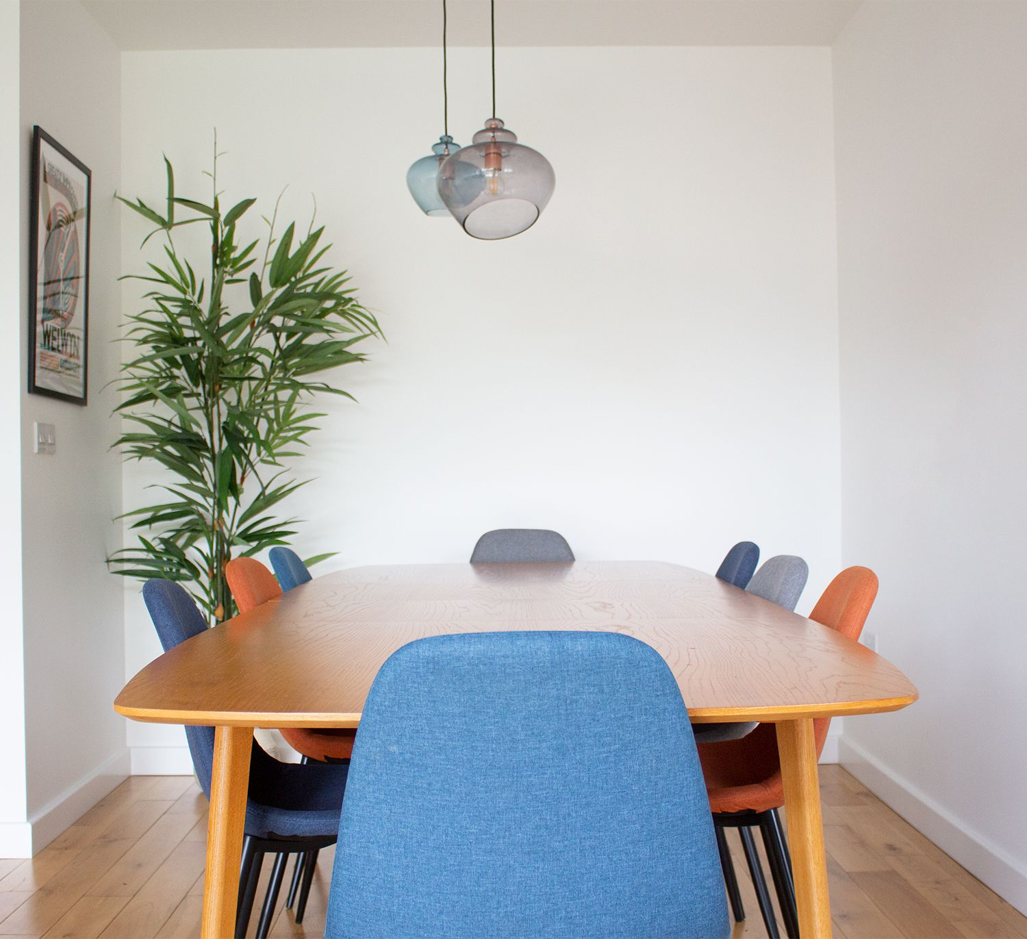 A photo of the mid century style dining table with upholstered chairs in blue, orange and grey.