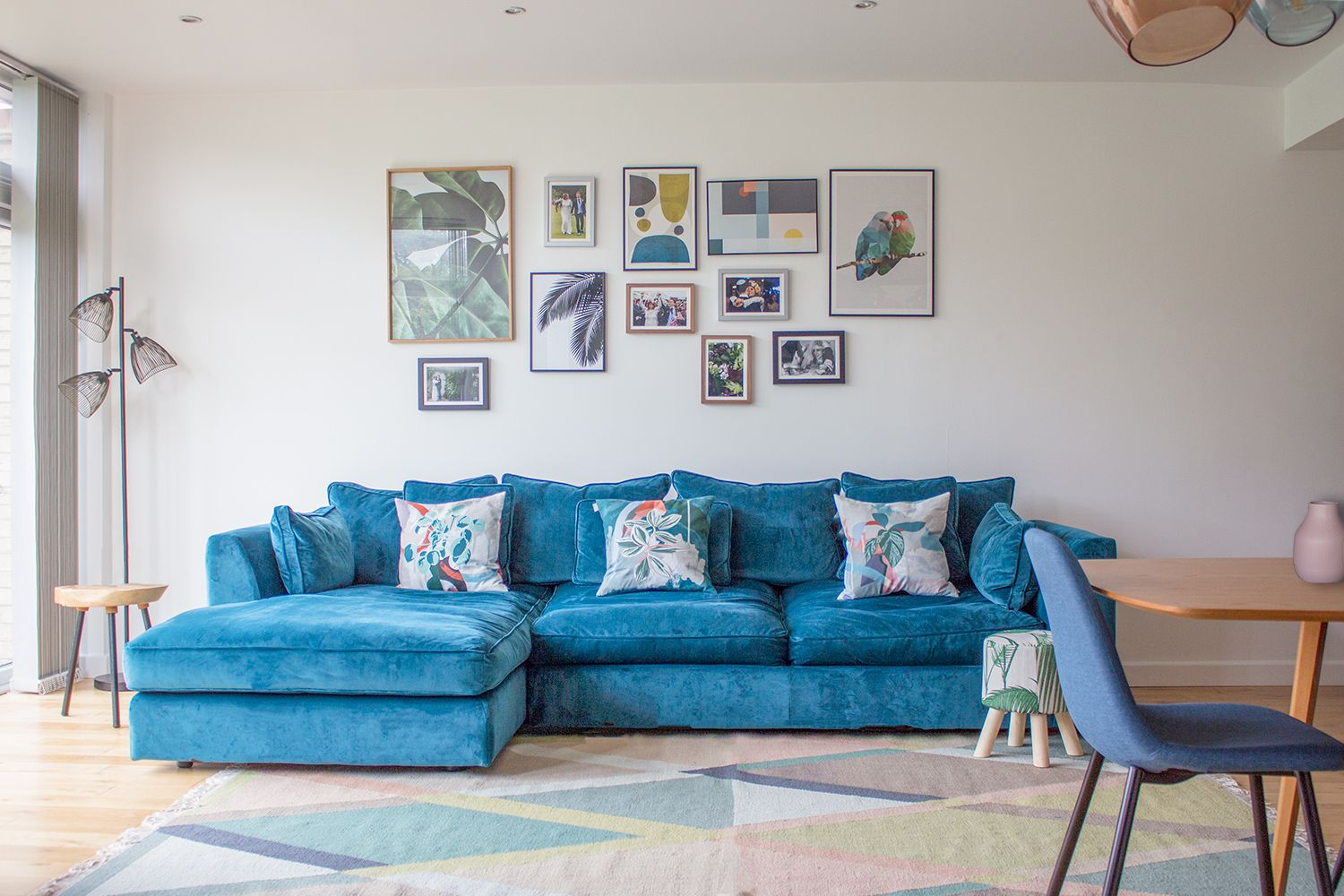 A photo of a teal velvet sofa in a room painted off white and on a colourful geometric rug.