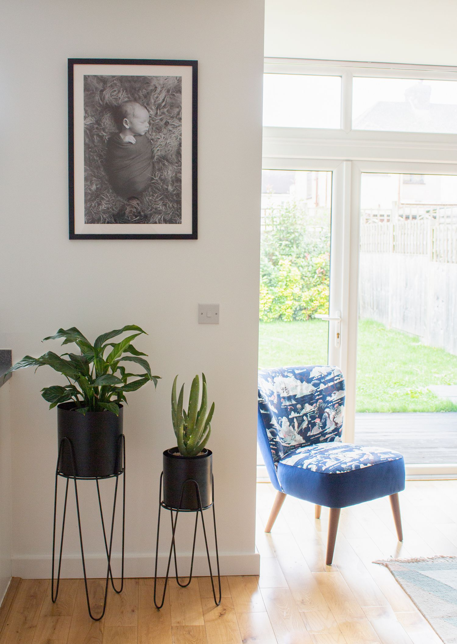 A photo of the chair by the windows, with two black planters and a personal photo on the wall.