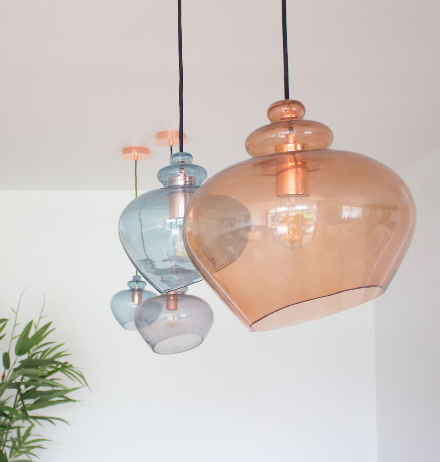 A close up of the four glass blown pendant lights in orange and blue.