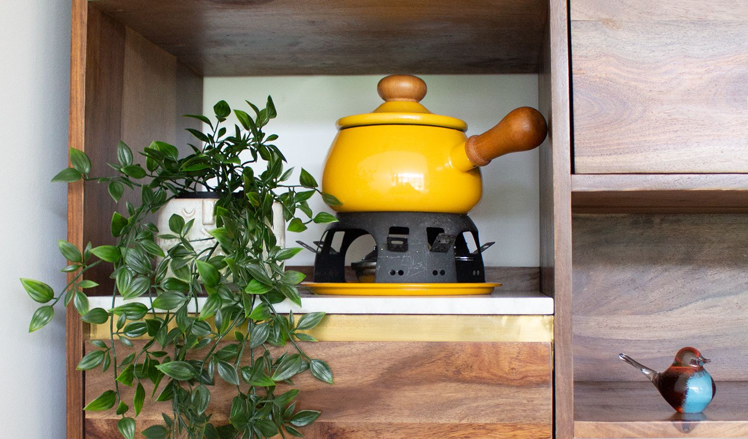A close up of the walnut shelf unit, styled with plants and a yellow fondue set.