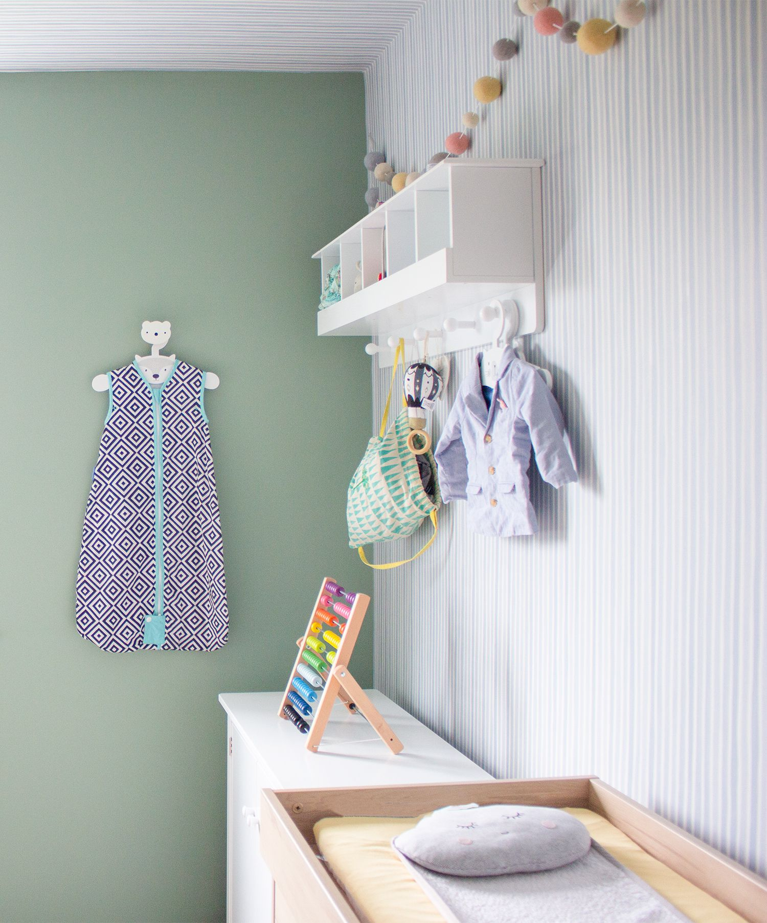 A view of the striped wallpaper wall with a white dresser and shelving above.